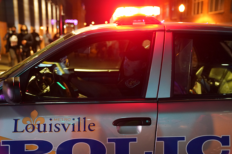 A police officer observes protesters, Thursday, September 24, in Louisville, Kentucky.