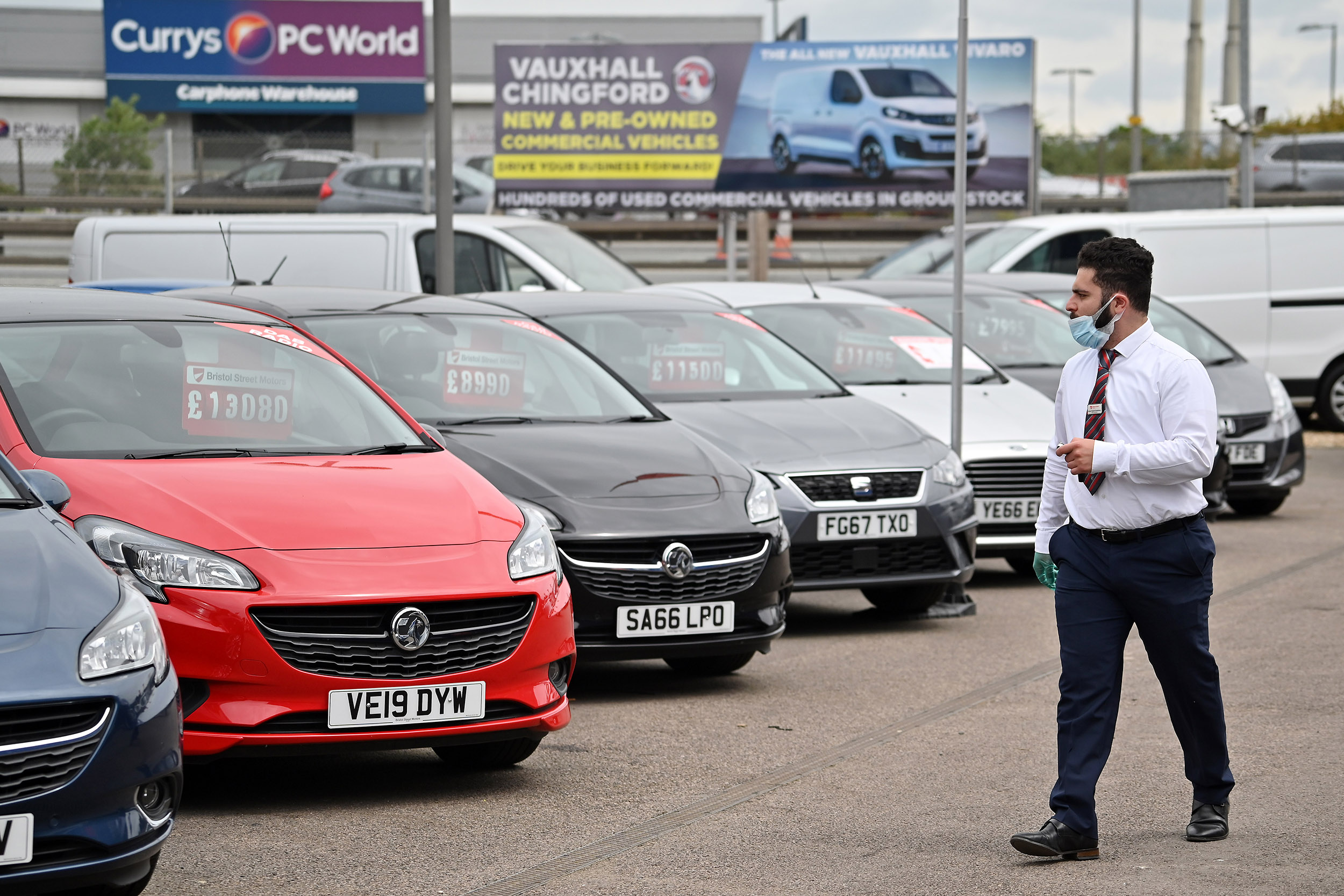 A car salesperson wearing PPE (personal protective equipment) walks past vehicles parked at the Vauxhall car dealership on June 4, in London, England.