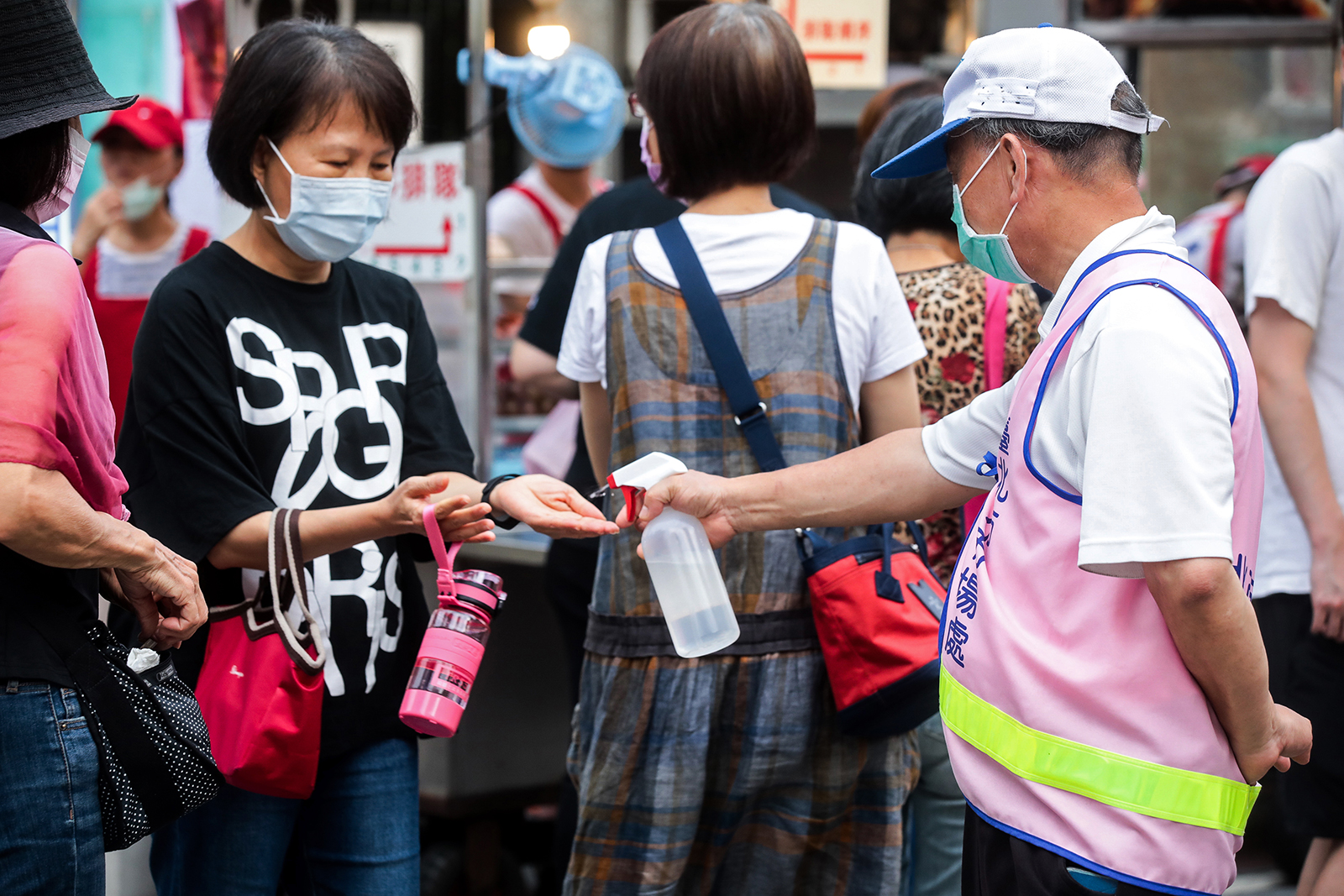 A municipal worker sprays sanitizer into a woman's hands at the entrance to the Ningxia Night Market in Taipei, Taiwan, on July 30.