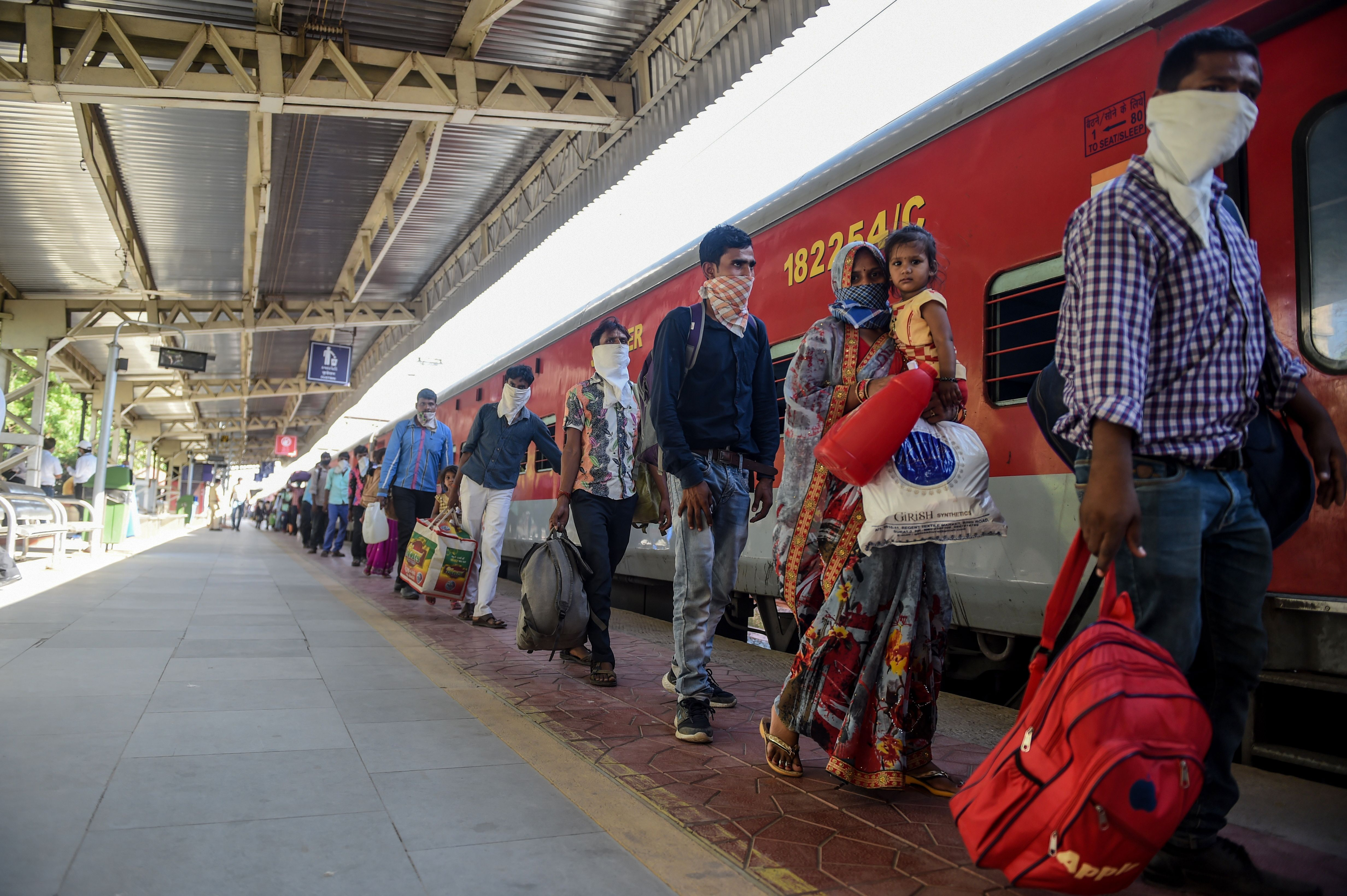 Migrant workers queue to board a special train going to Agra in Uttar Pradesh state during a government-imposed nationwide lockdown at Sabarmati Railway Station on the outskirts of Ahmedabad on May 2.