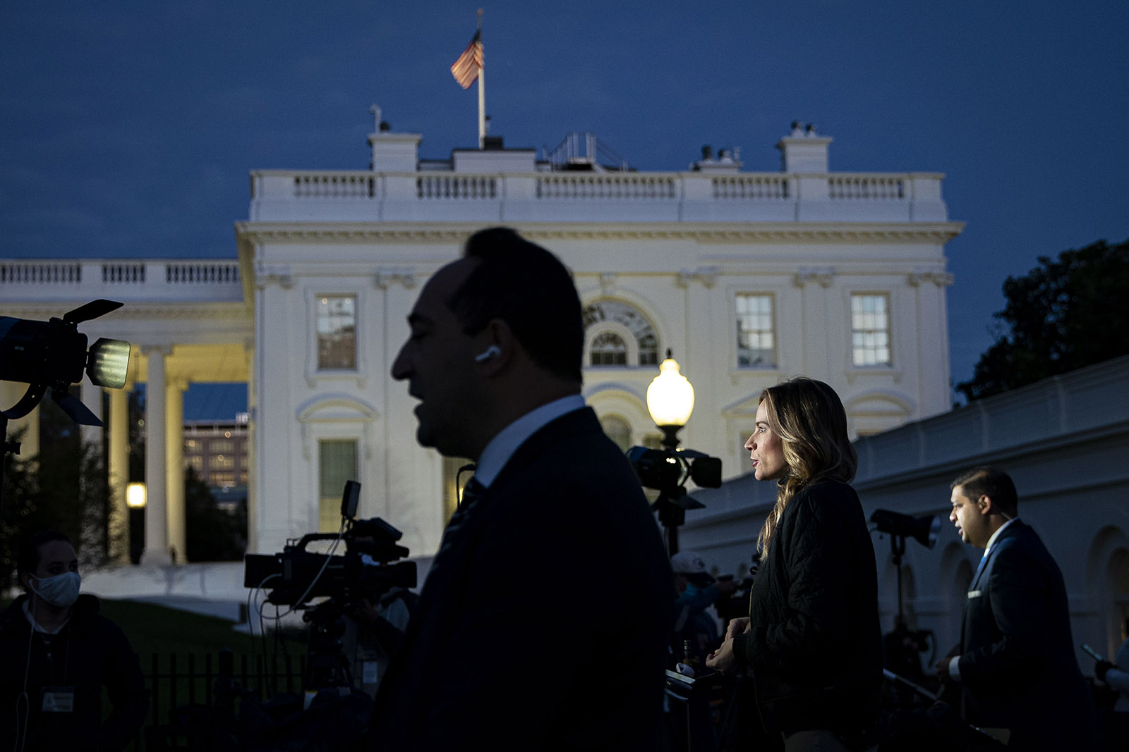 Members of the media report outside of the White House in Washington on Tuesday.