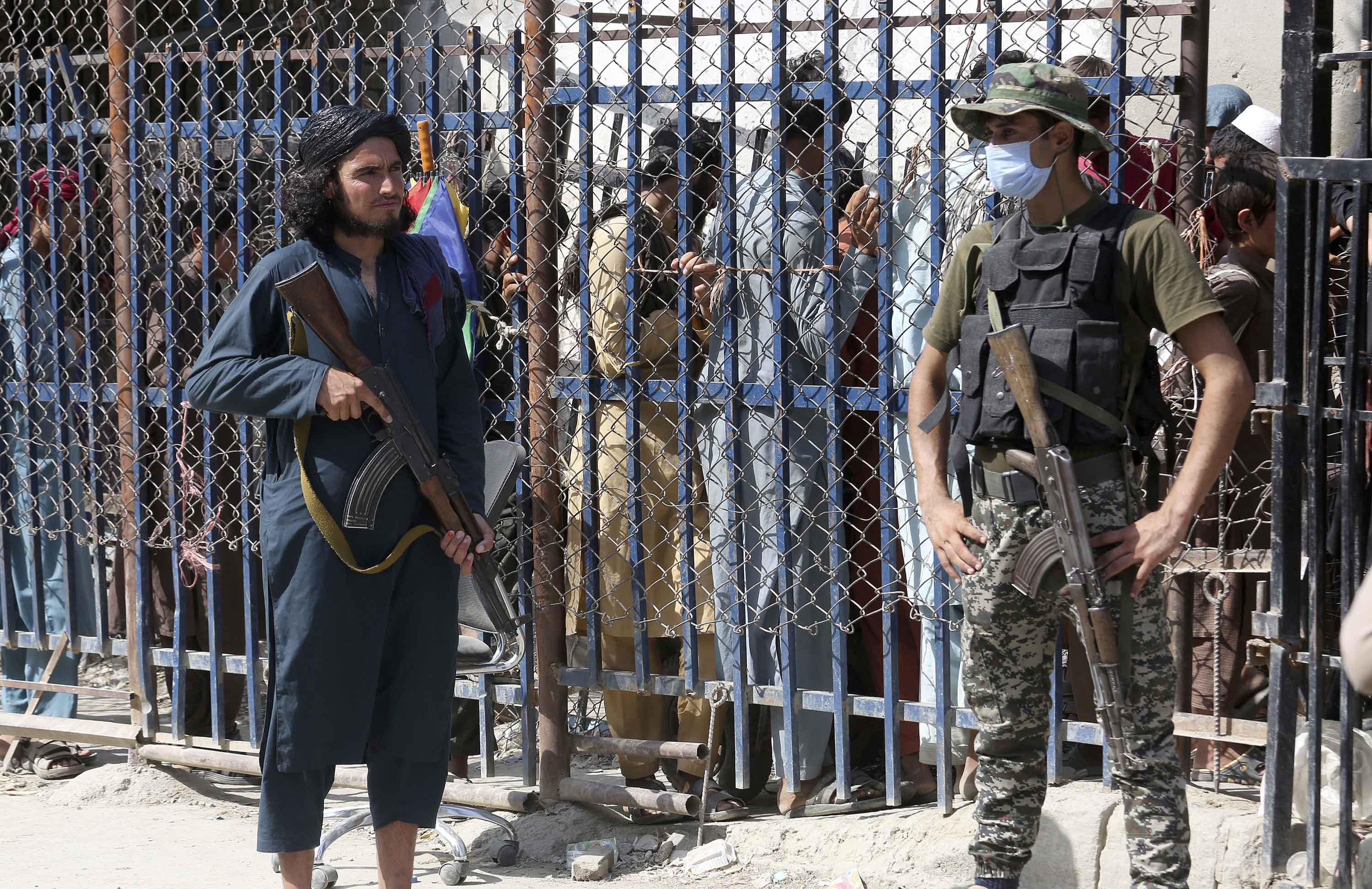 A Taliban fighter, left, and Pakistani paramilitary soldier stand guard on their respective sides of the border crossing between Pakistan and Afghanistan, in Torkham, Pakistan, on August 21.