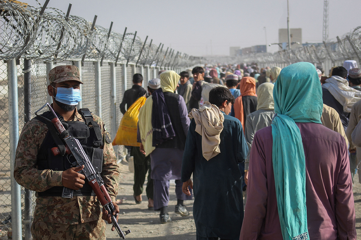A Pakistani soldier stands guard as Afghans walk along fences after arriving in Pakistan through the Pakistan-Afghanistan border crossing point in Chaman on August 26.
