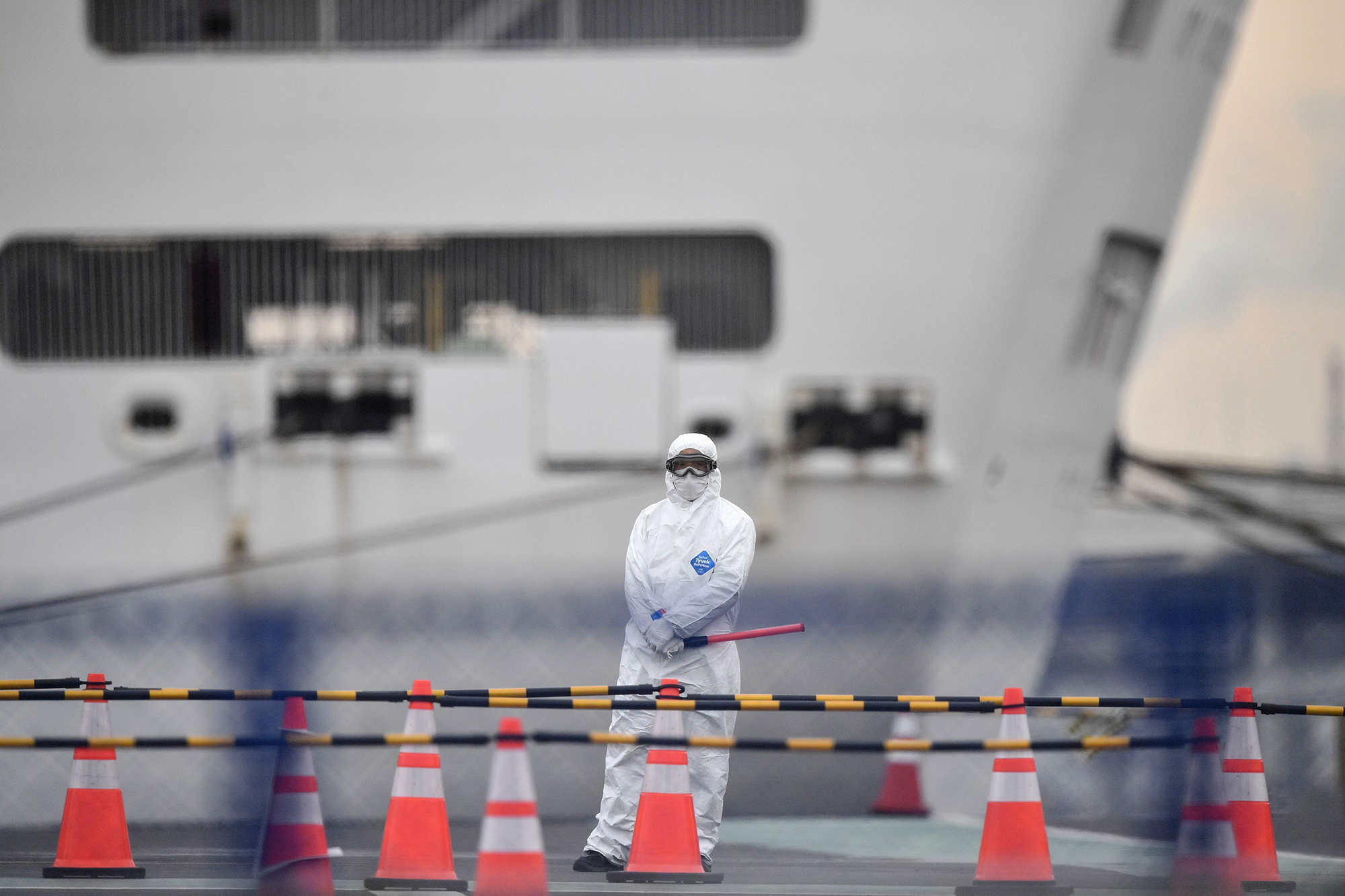 An official in protective gear stands near the Diamond Princess cruise ship, quarantined at Yokohama Port in Yokohama, Japan, on Thursday, February 20.