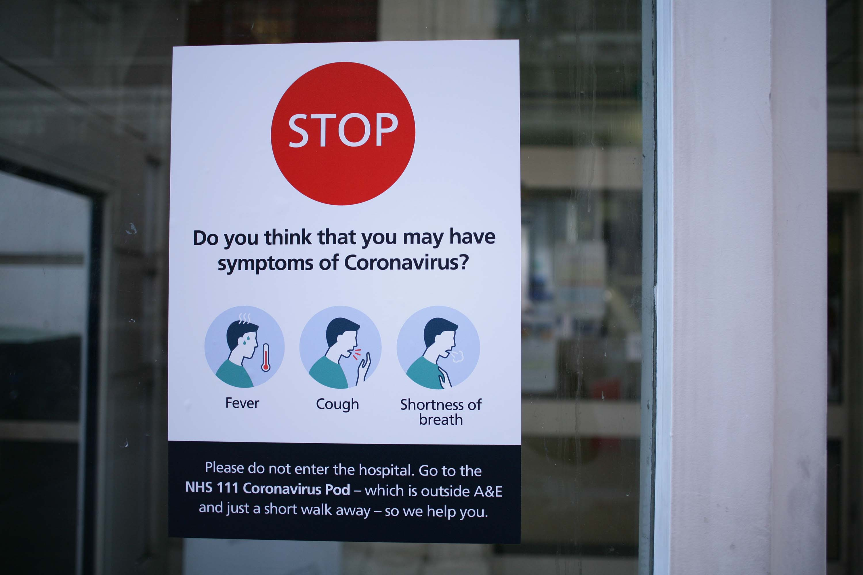 A notice instructs people experiencing symptoms of the coronavirus not to enter St. Mary's Hospital in London, England, on March 11. The hospital houses a dedicated 'coronavirus pod' isolation unit for symptomatic patients.