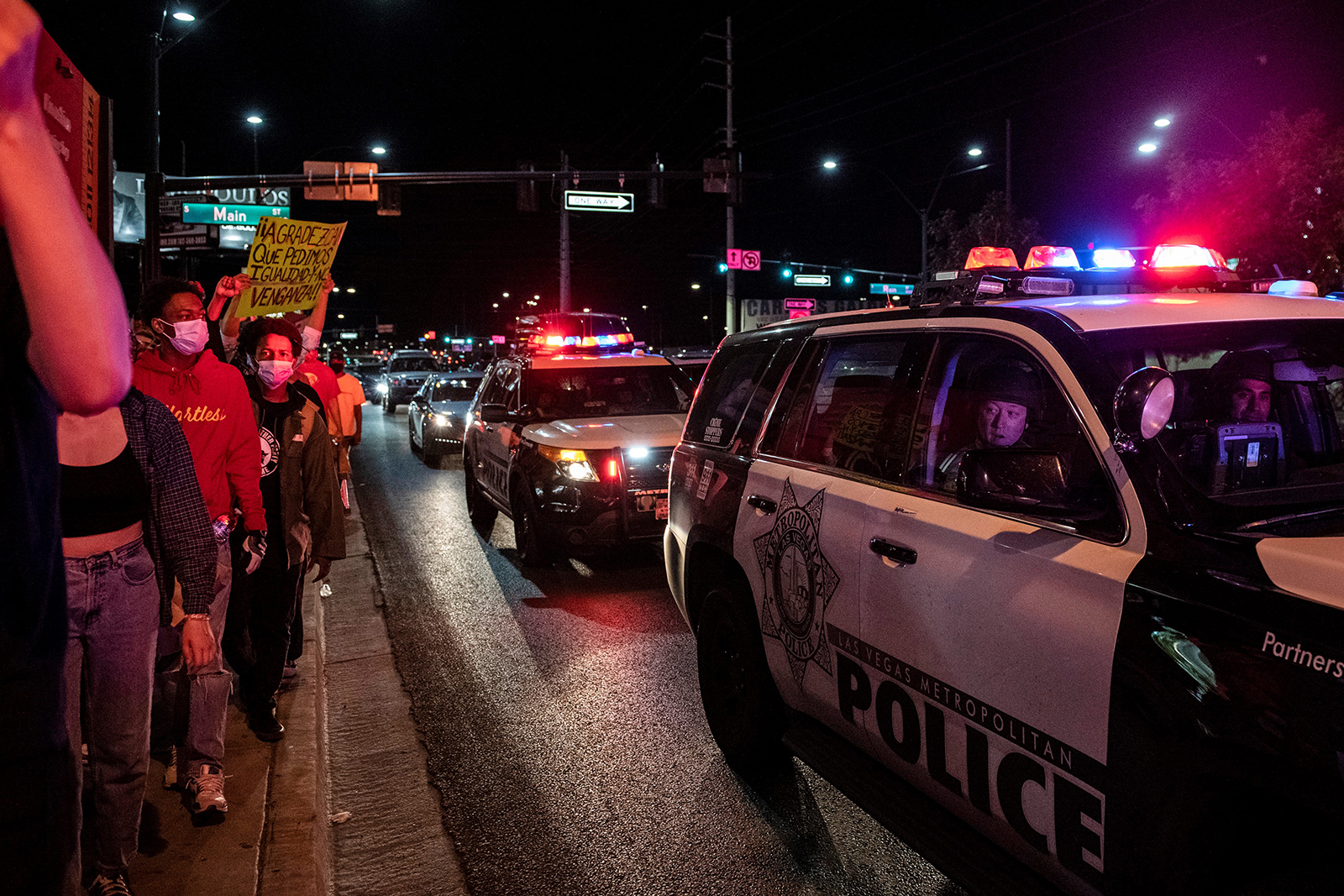 A police officer looks outside the car window as people march, on June 1, in downtown Las Vegas.