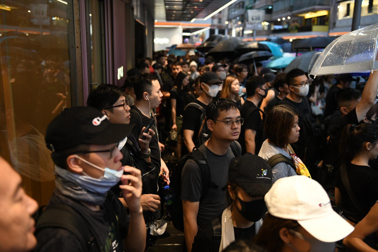 Some protesters shelter in doorways in Hong Kong.