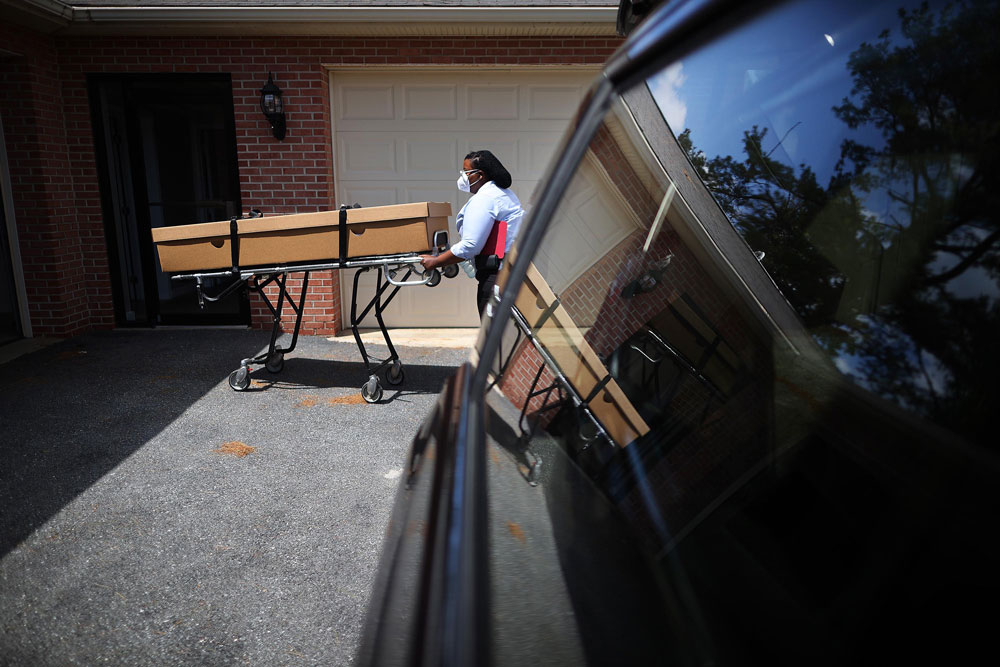 A Maryland Cremation Services transporter loads the remains of a coronavirus victim into her vehicle at Stauffer Funeral Home on May 12, in Frederick, Virginia.