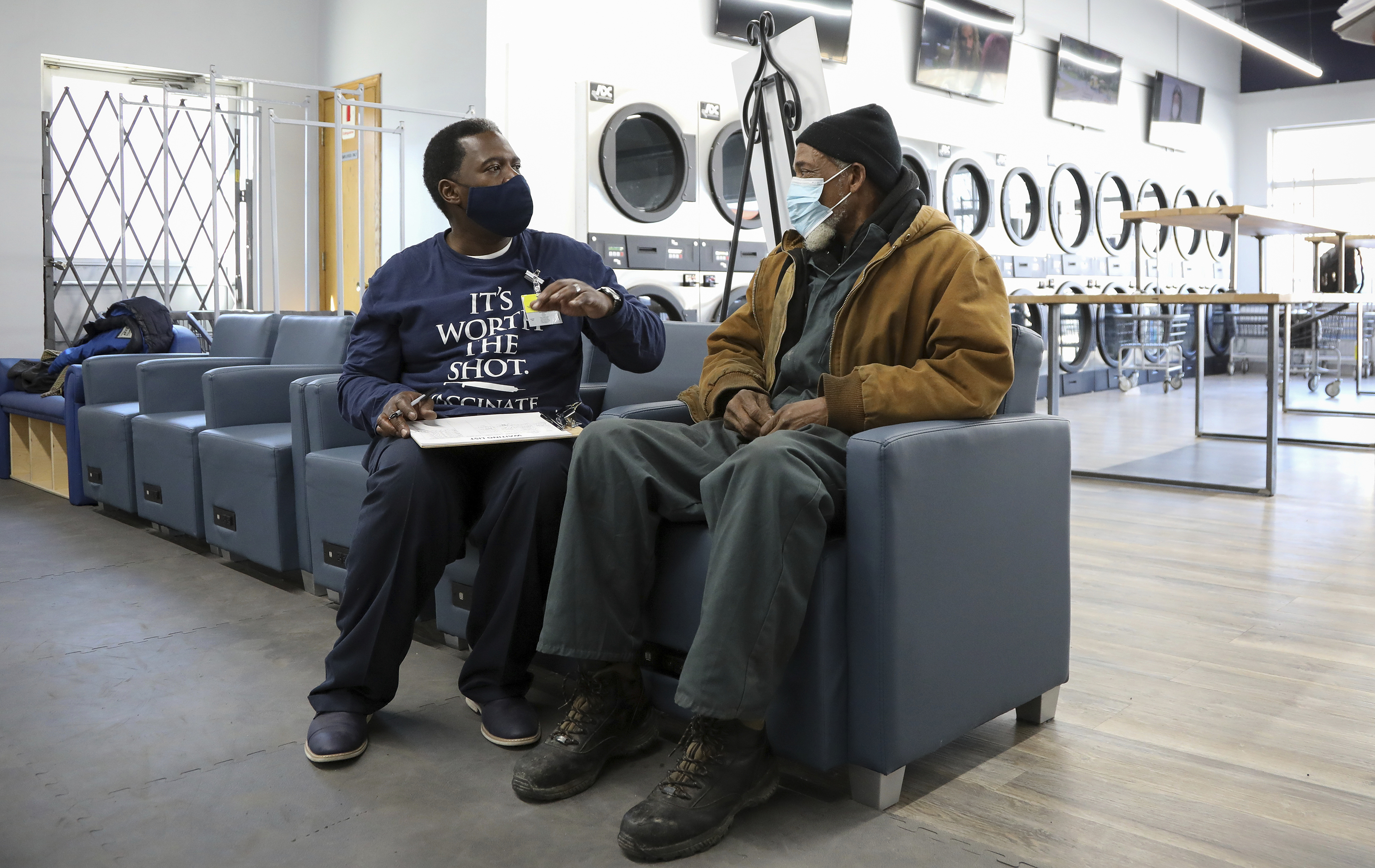 Community outreach worker Herman Simmons, left, makes a vaccination appointment for Theopulis Polk, right, at a Chicago laundromat on Saturday, March 6.