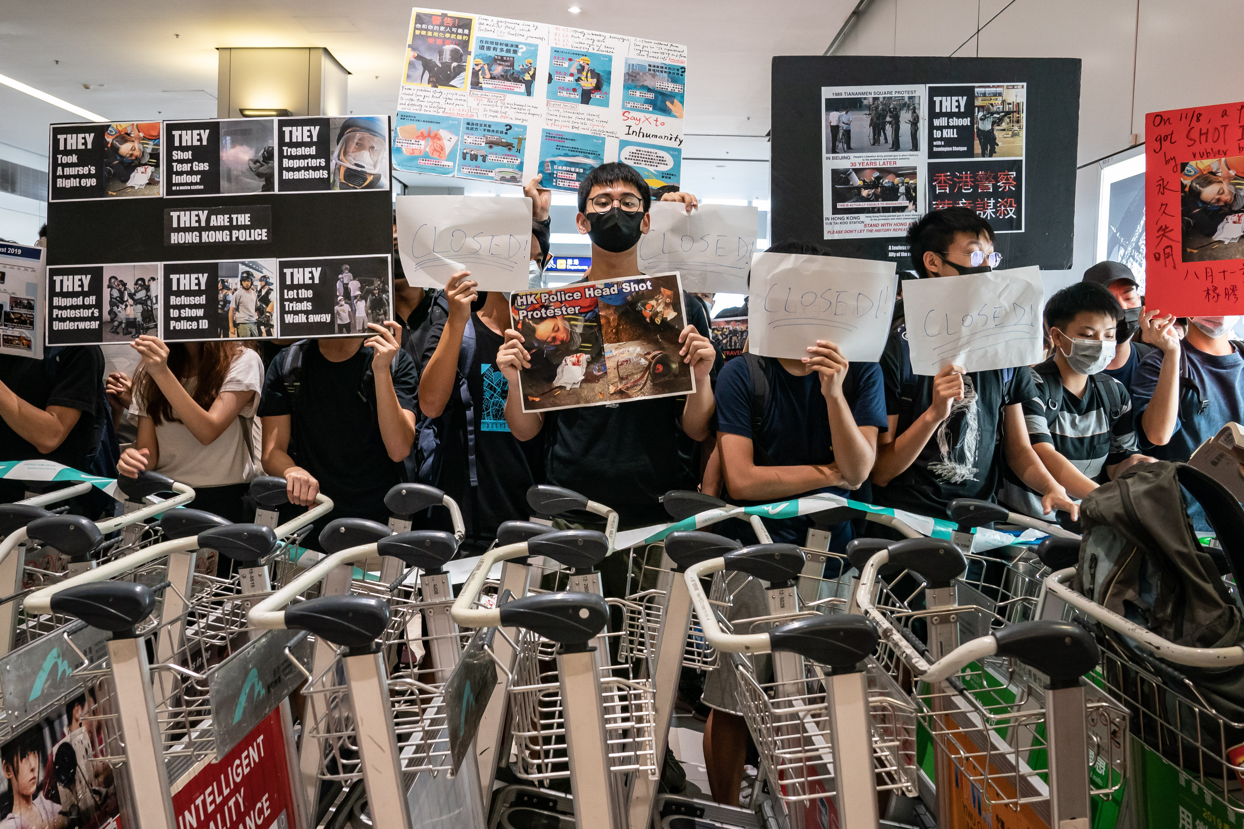 Protesters hold placards as they block the departure gate of the Hong Kong International Airport Terminal 2 during a demonstration on August 13.