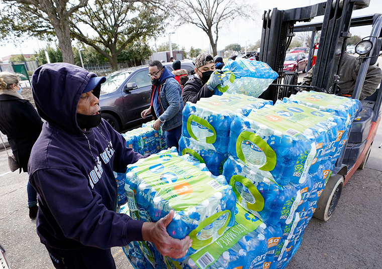 Donated water is distributed to residents, Thursday, February 18, in Houston. Houston and several surrounding cities are under a boil water notice as many residents are still without running water in their homes.