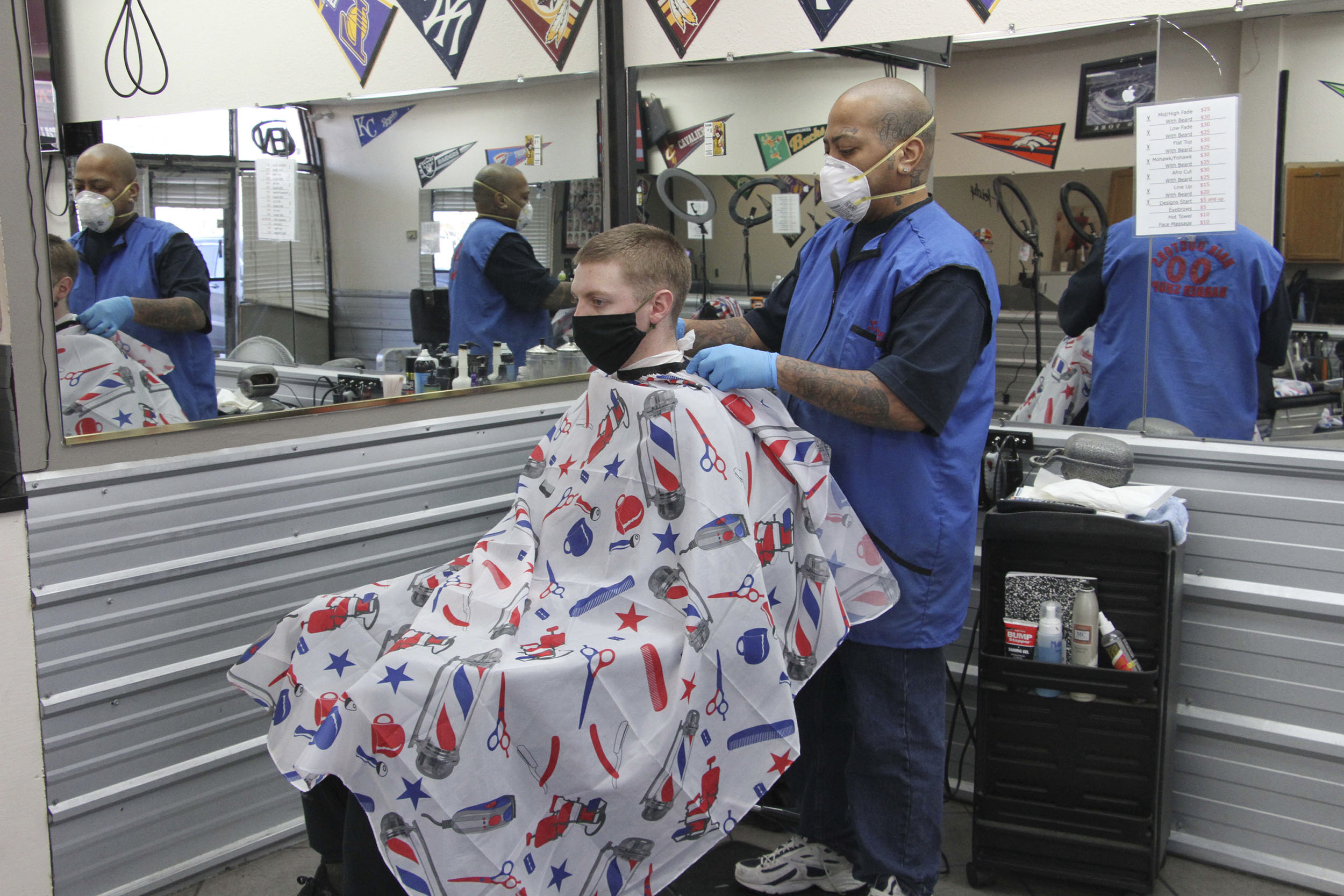 Larry Love, right, the manager at Hair Doctors in Anchorage, Alaska, gives an airman a haircut on Monday, April 27.