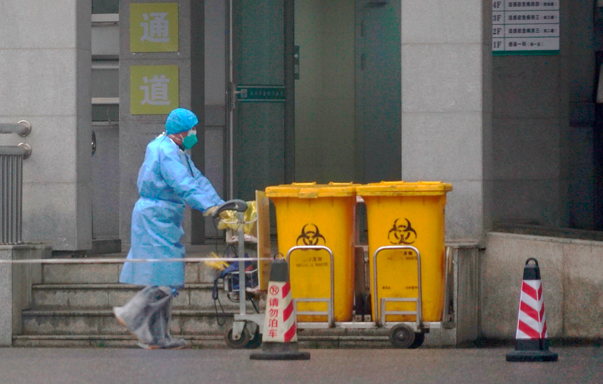 Staff move bio-waste containers past the entrance of the Wuhan Medical Treatment Center.