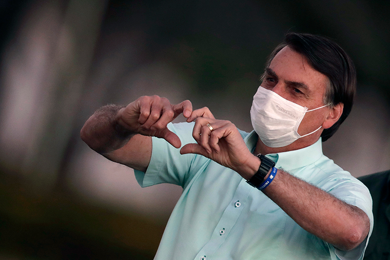Brazil's President Jair Bolsonaro wears a protective face mask as he makes a heart-hand sign to supporters during a Brazilian flag retreat ceremony outside his official residence the Alvorada Palace, in Brasilia, Brazil, Wednesday, July 22.