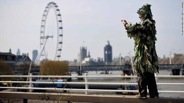 A man dressed as a tree takes a photo of the protest on Waterloo Bridge, with the London Eye and Houses of Parliament in the backdrop.