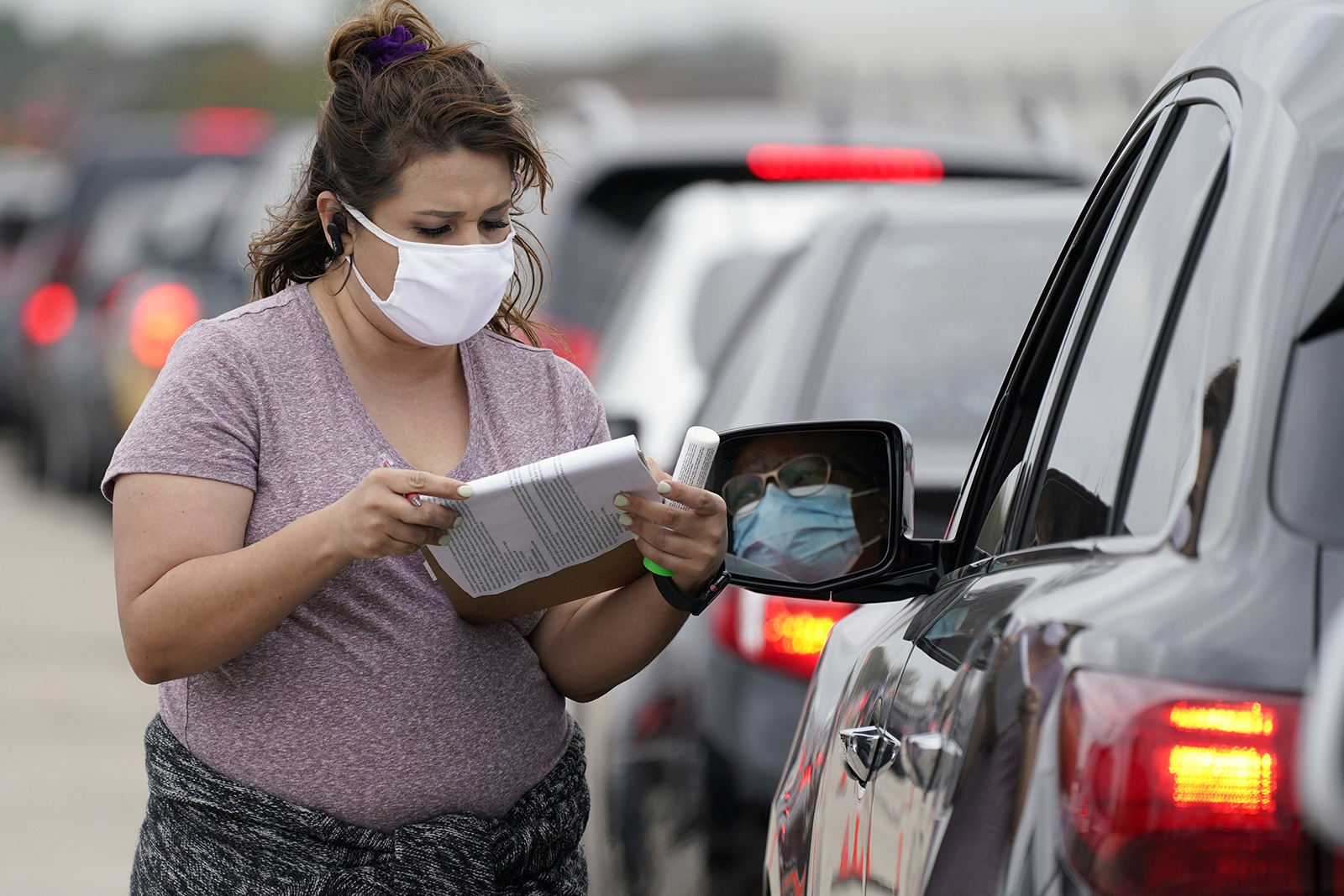 Volunteer Daisy Valdivia, left, of Forth Worth, Texas, takes down information from a person waiting in line to receive food items during a Tarrant Area Food Bank mobile pantry distribution event in Arlington, Texas, Friday, Nov. 20, 2020. Thanksgiving holiday food items were distributed to over 5,000 families during the event that took place in a parking lot outside AT&T Stadium. (AP Photo/Tony Gutierrez)