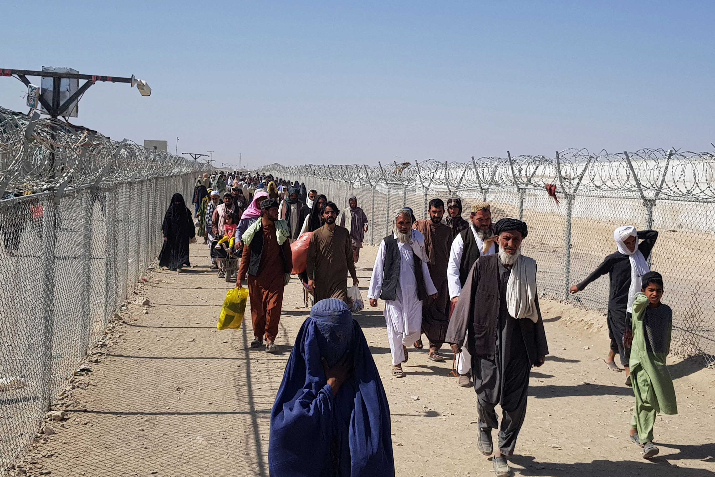 Afghan nationals cross the border into Chaman, Pakistan on August 18, 2021.