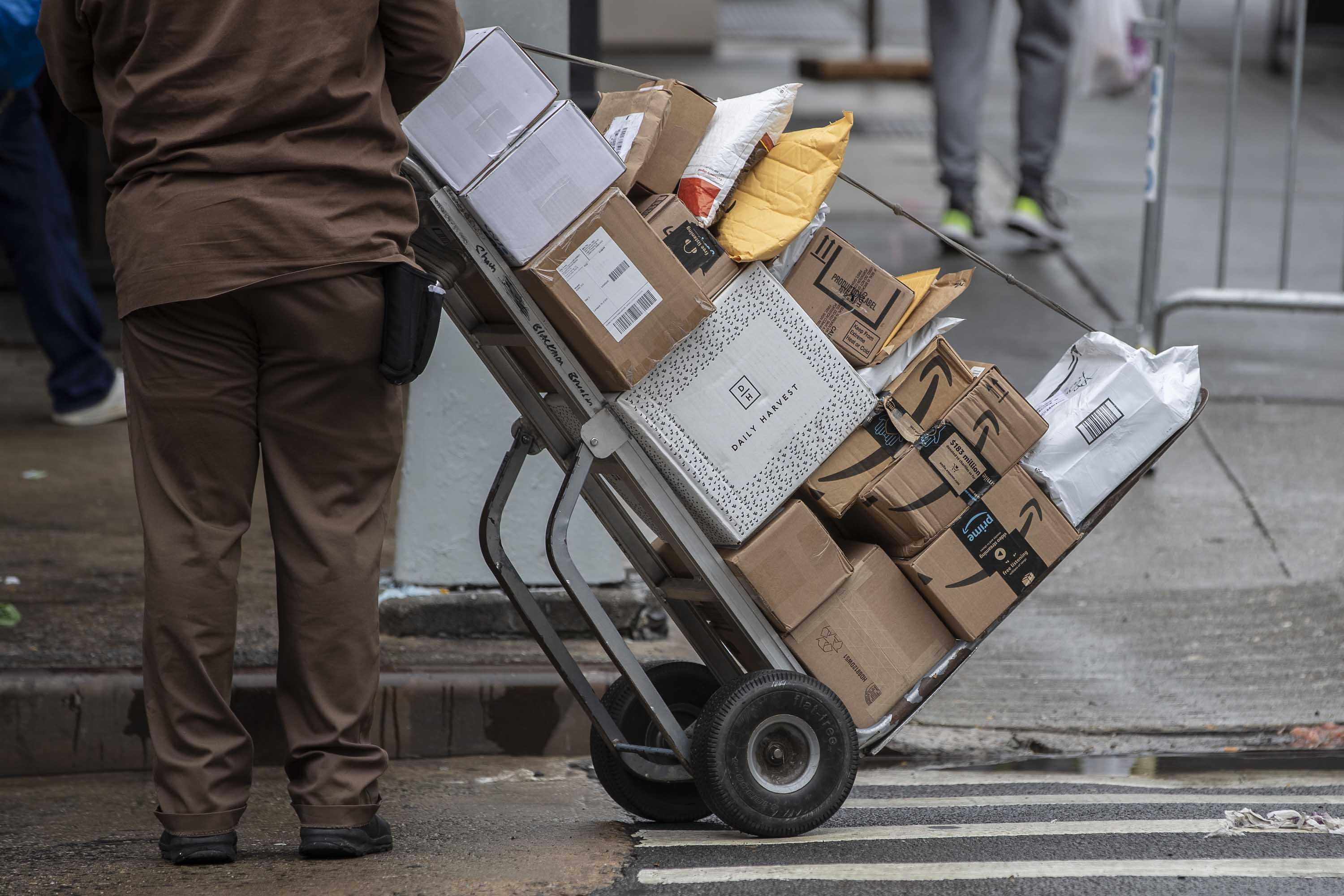 A UPS driver pushes a trolley with packages during a delivery in New York, on October 13.