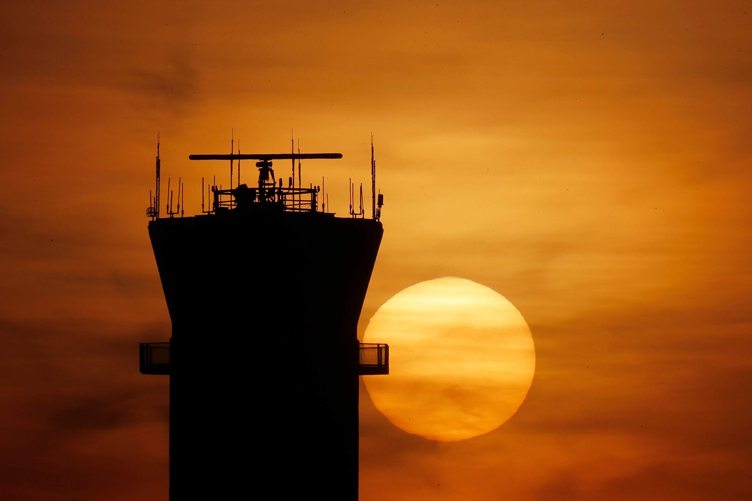 The sun sets behind the air traffic control tower at Chicago Midway International Airport on Tuesday, March 17.