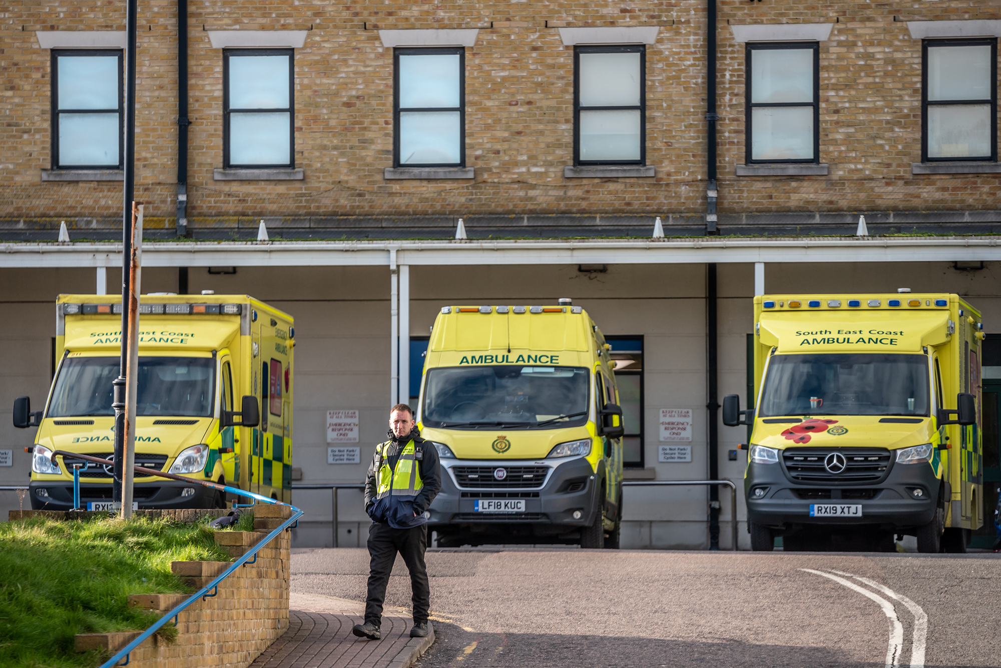A man walks past ambulances parked outside the Royal Sussex County Hospital where a third person has tested positive for coronavirus in the UK on February 6.