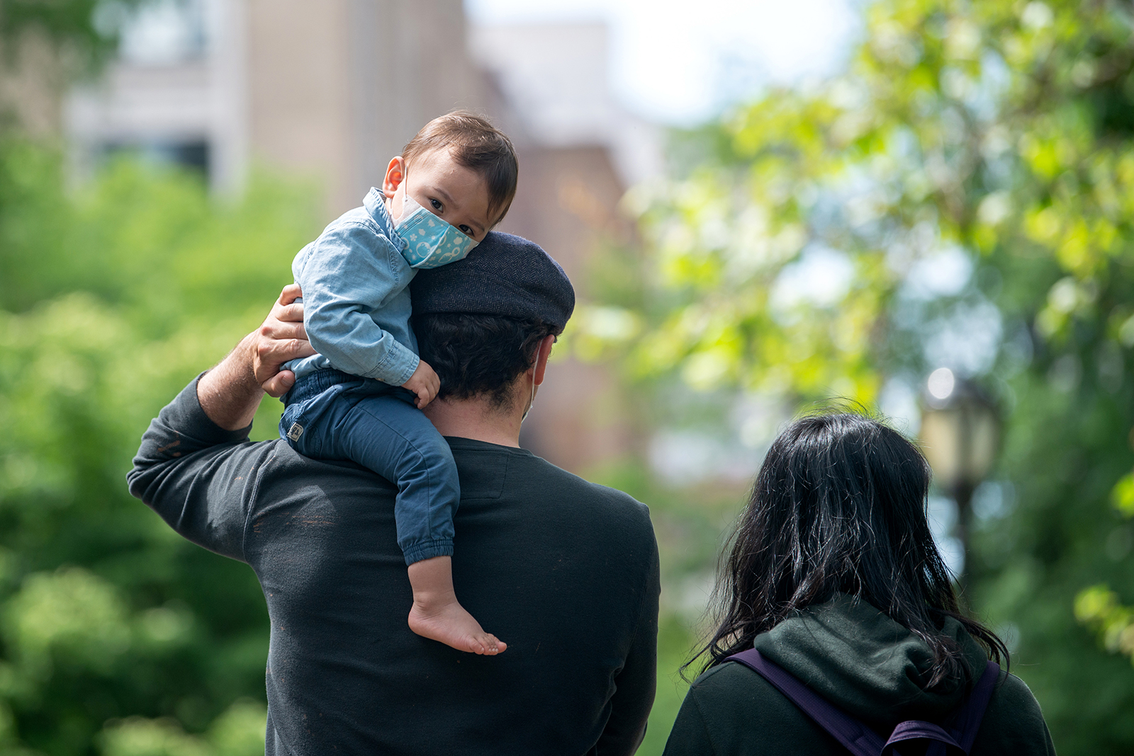 A youngster wearing a mask looks at the camera while sitting on his father's shoulder in Central Park in New York, on May 24.