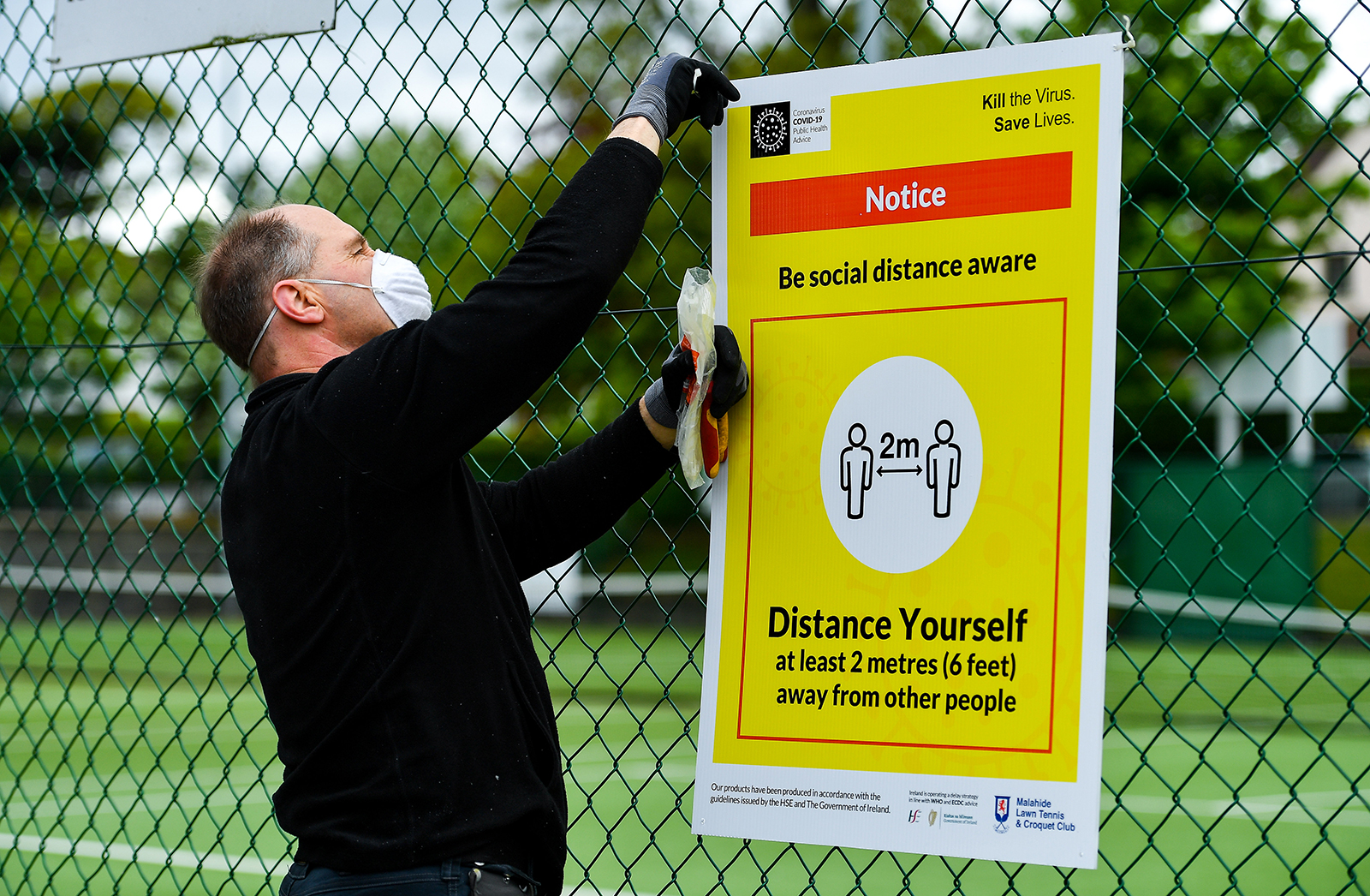 A man prepares social distancing signage at Malahide Lawn Tennis and Croquet Club in Dublin on Friday, May 15, as it prepares to re-open as one of the first sports allowed to resume having followed previous directives from the Irish Government.