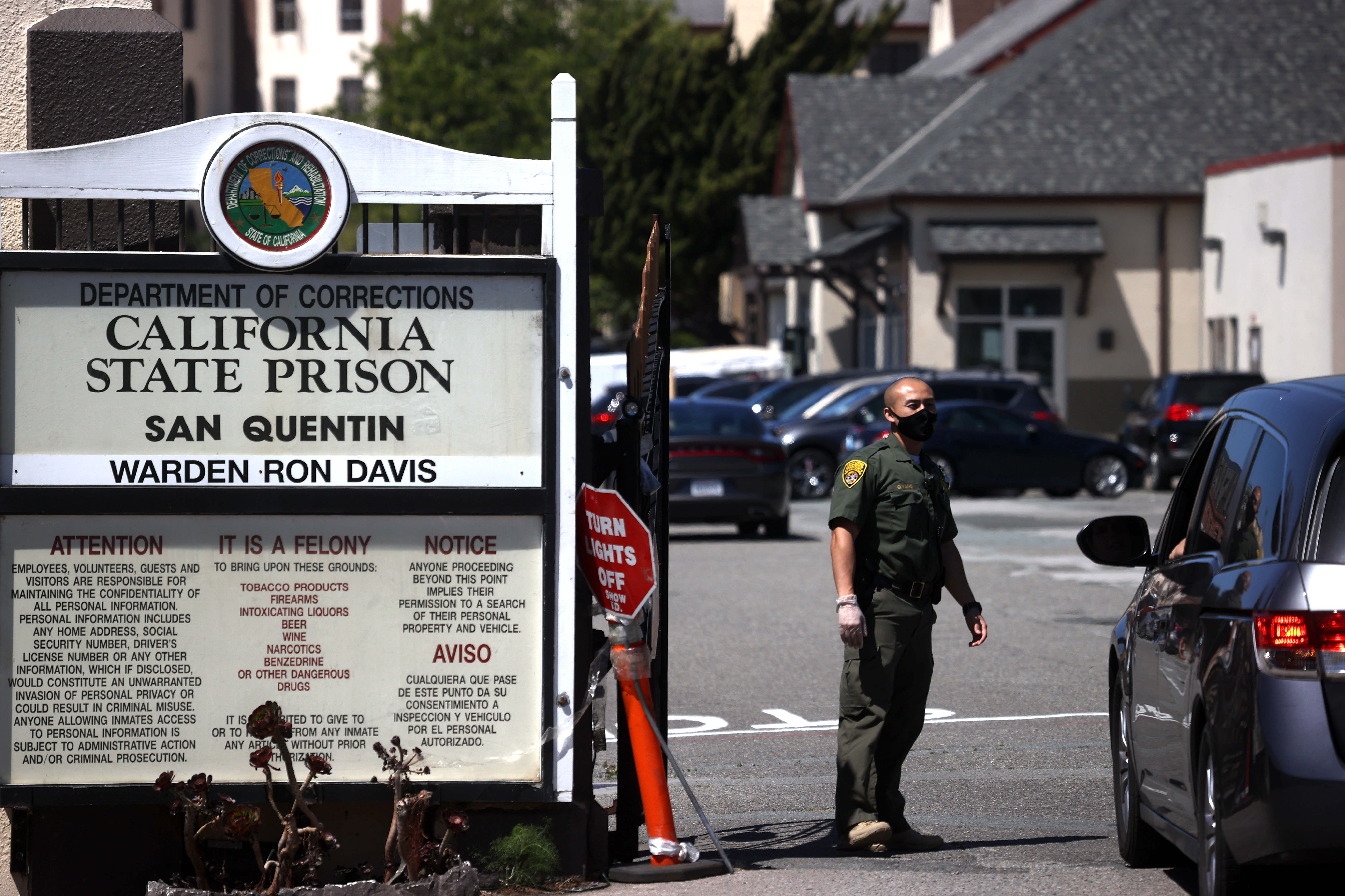 A California Department of Corrections and Rehabilitation officer wears a protective mask as he stands guard at the front gate of San Quentin State Prison on Monday, June 29, in San Quentin, California.