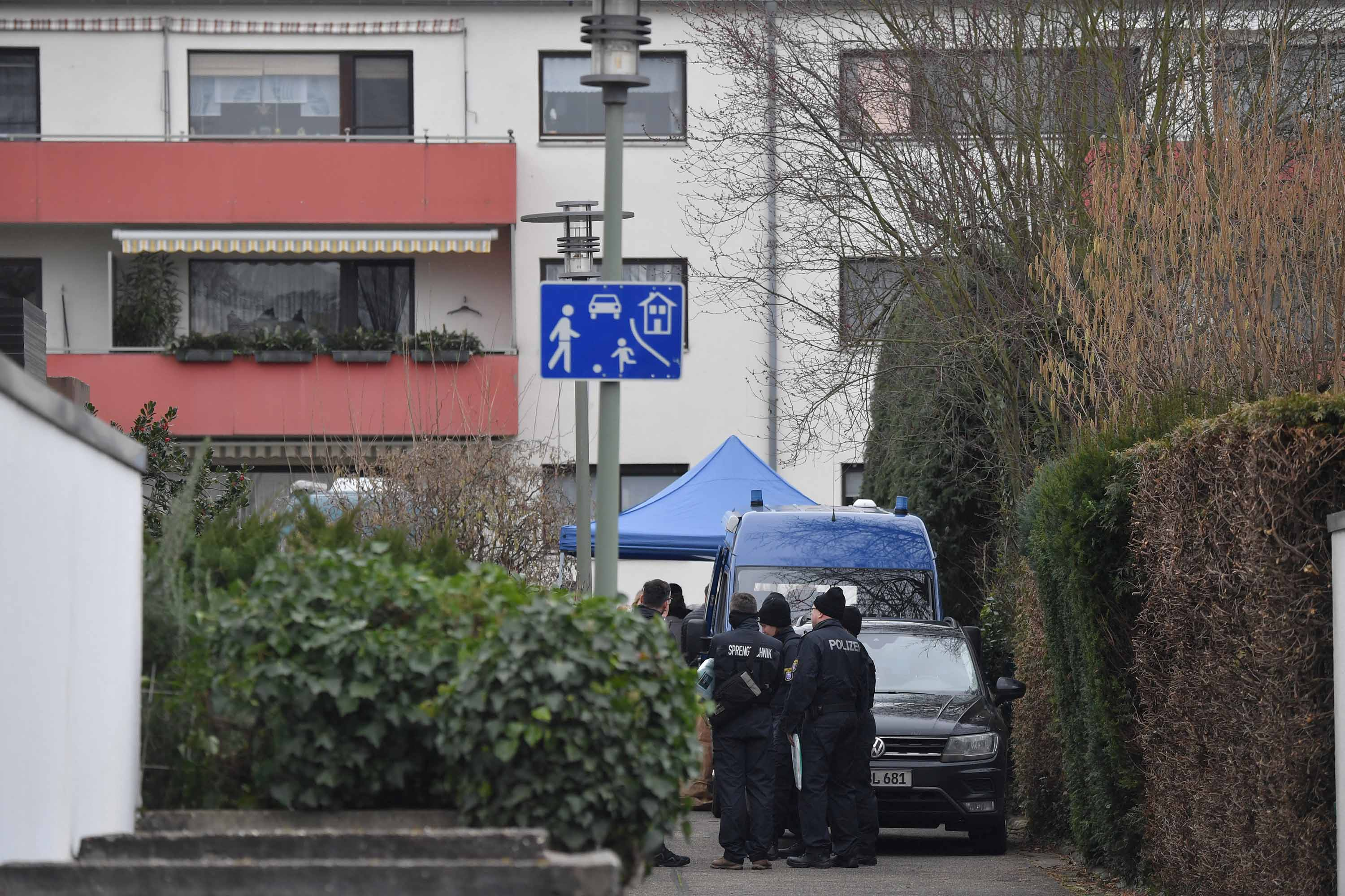 Police officers stand by the house where the suspect was found dead in Hanau, Germany.