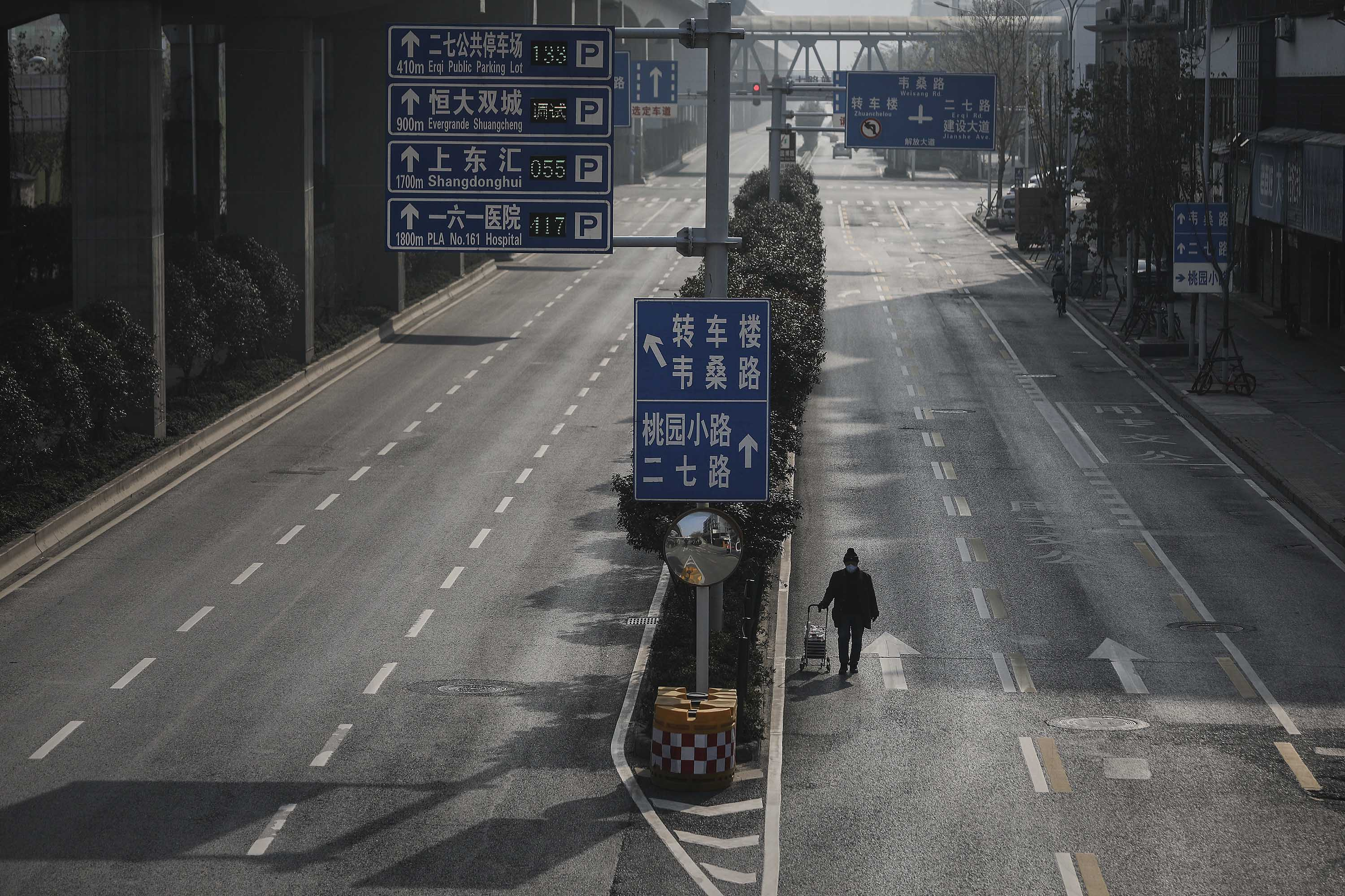 A man drags a handcart across an empty road in Wuhan on February 5.