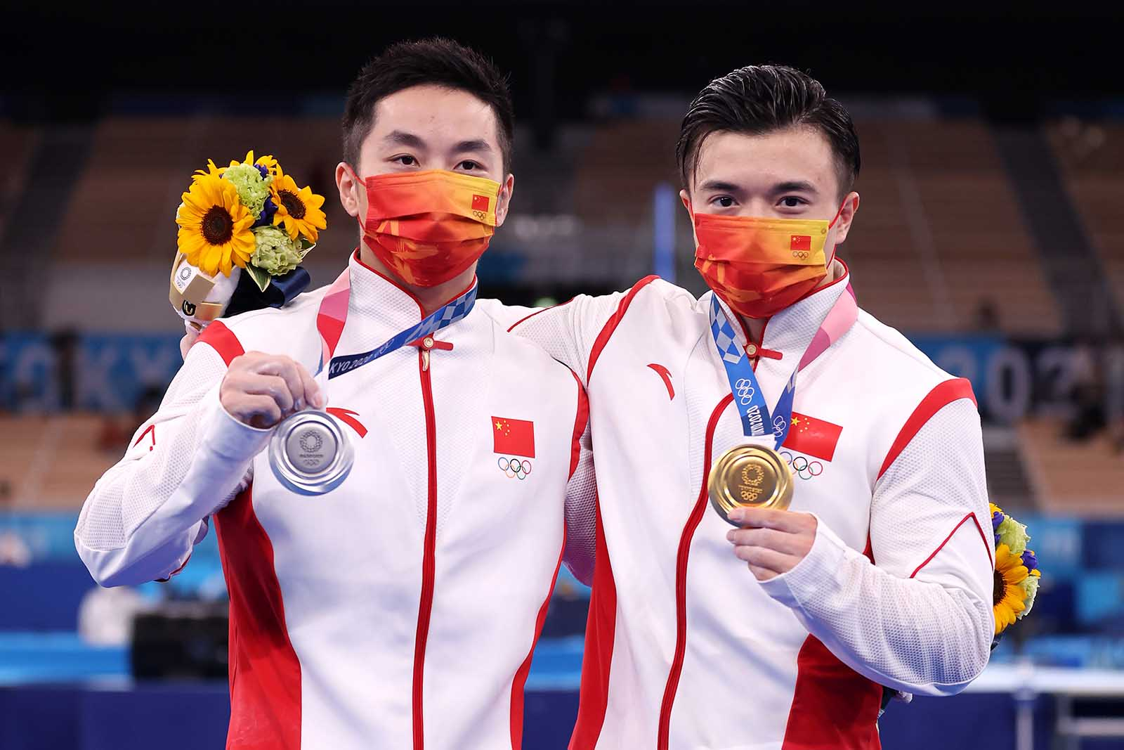 You Hao, left, and Liu Yang of Team China display their medals following the men's rings competition on August 2.