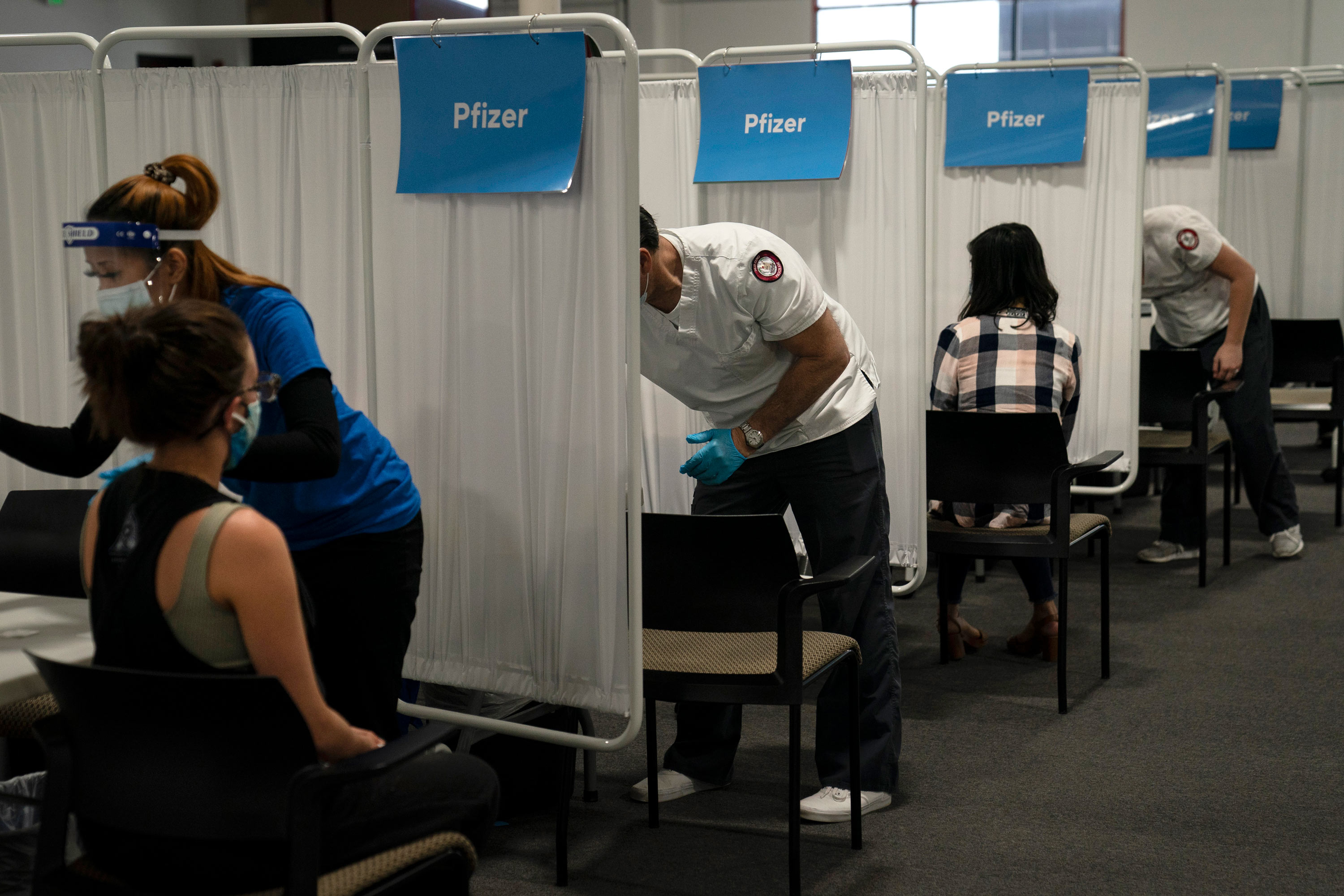 Student nurse Dario Gomez, center, disinfects a chair after administering the Pfizer COVID-19 vaccine to a patient at Providence Edwards Lifesciences vaccination site in Santa Ana, California, on May 21.