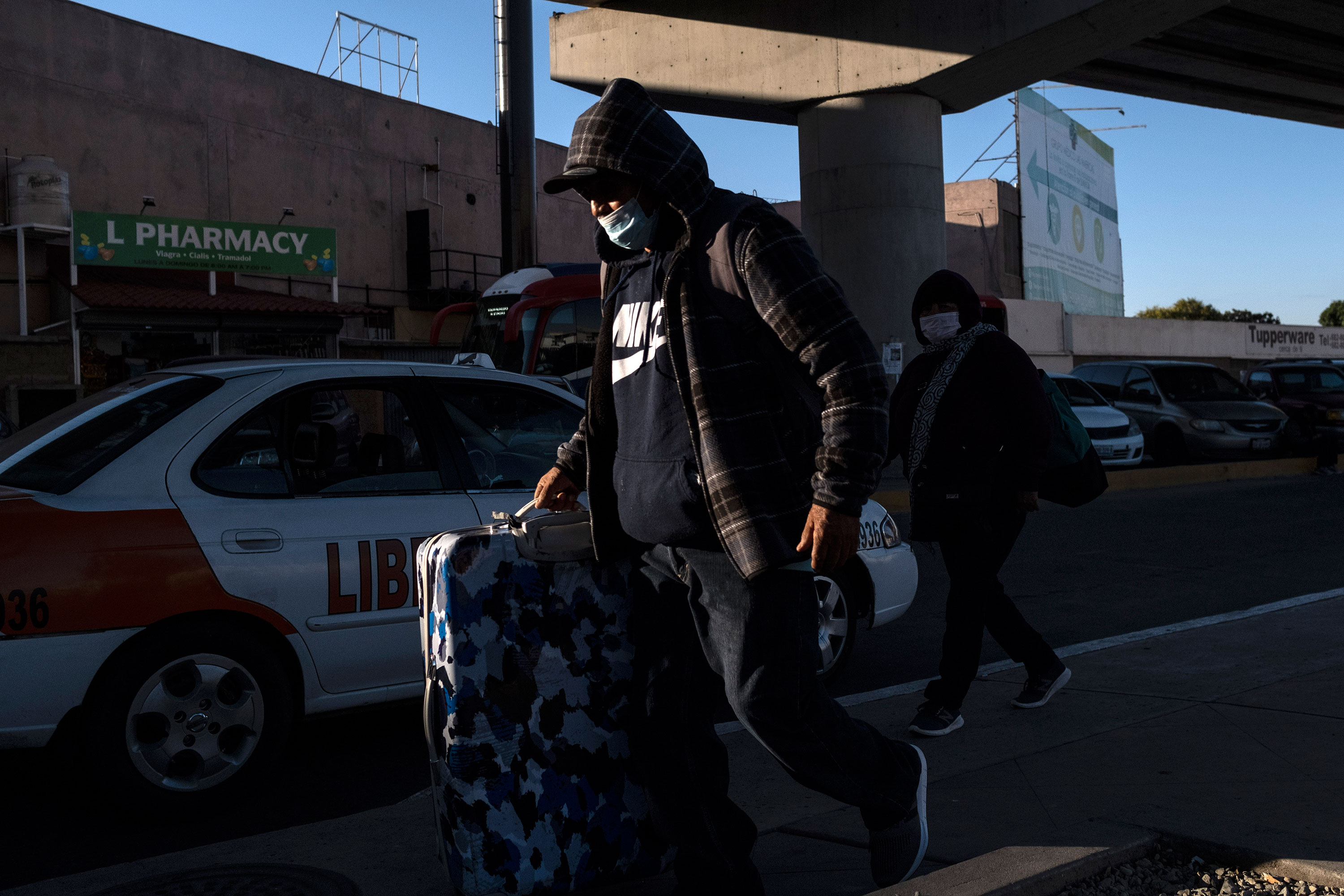 A couple wearing protective masks walks towards the El Chaparral crossing port on the US/Mexico Border in Tijuana, Mexico, on February 29.