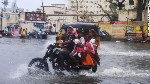 Indian residents ride on a bike along a flooded road after Cyclone Fani landfall in Puri on May 3, 2019.