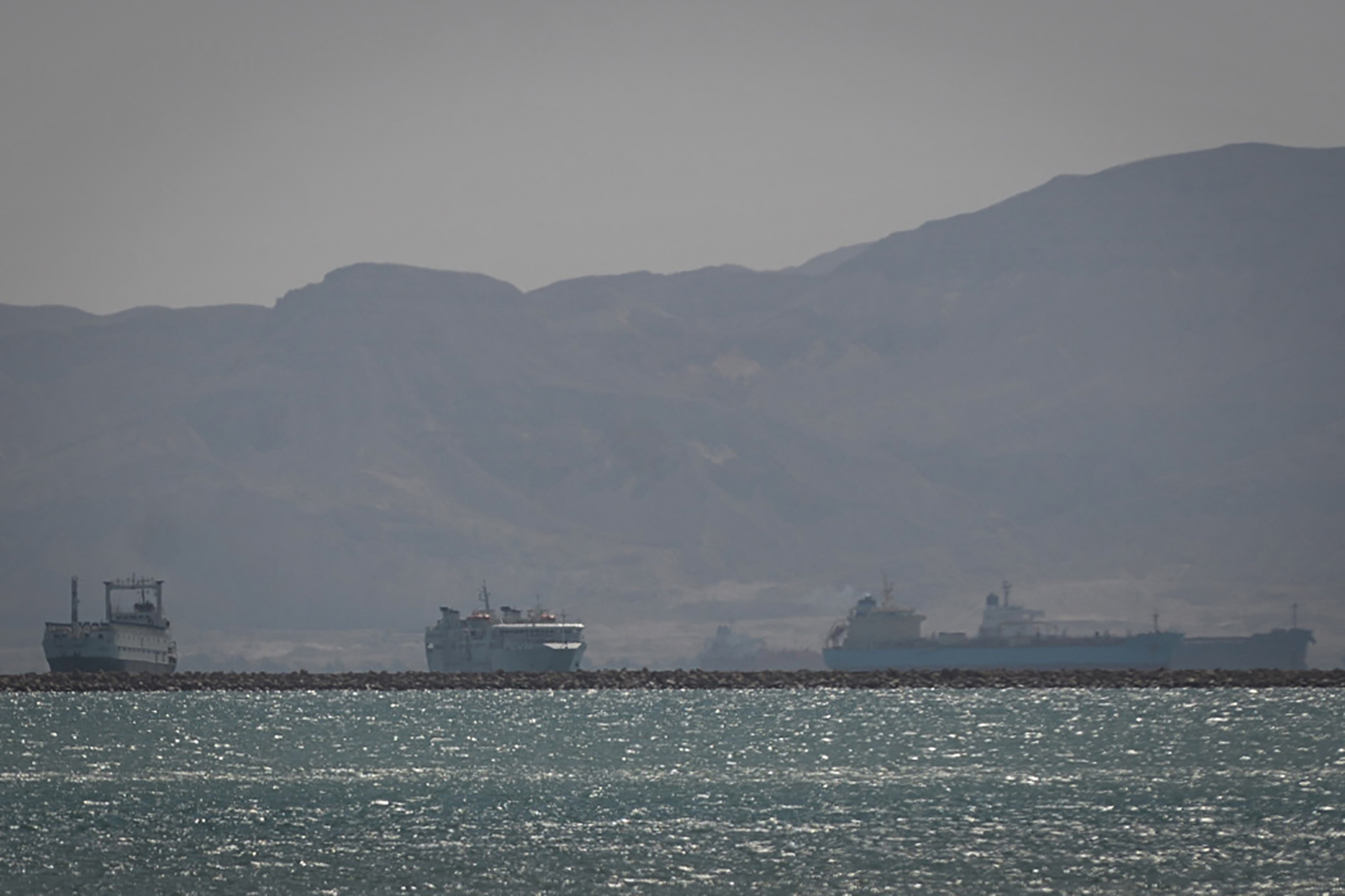 "Tugboats and vessels are seen sailing on the Suez Canal, shortly before the ""Ever Given"" container ship operated by the Evergreen Marine Corporation, was fully freed and floated, on March 29."