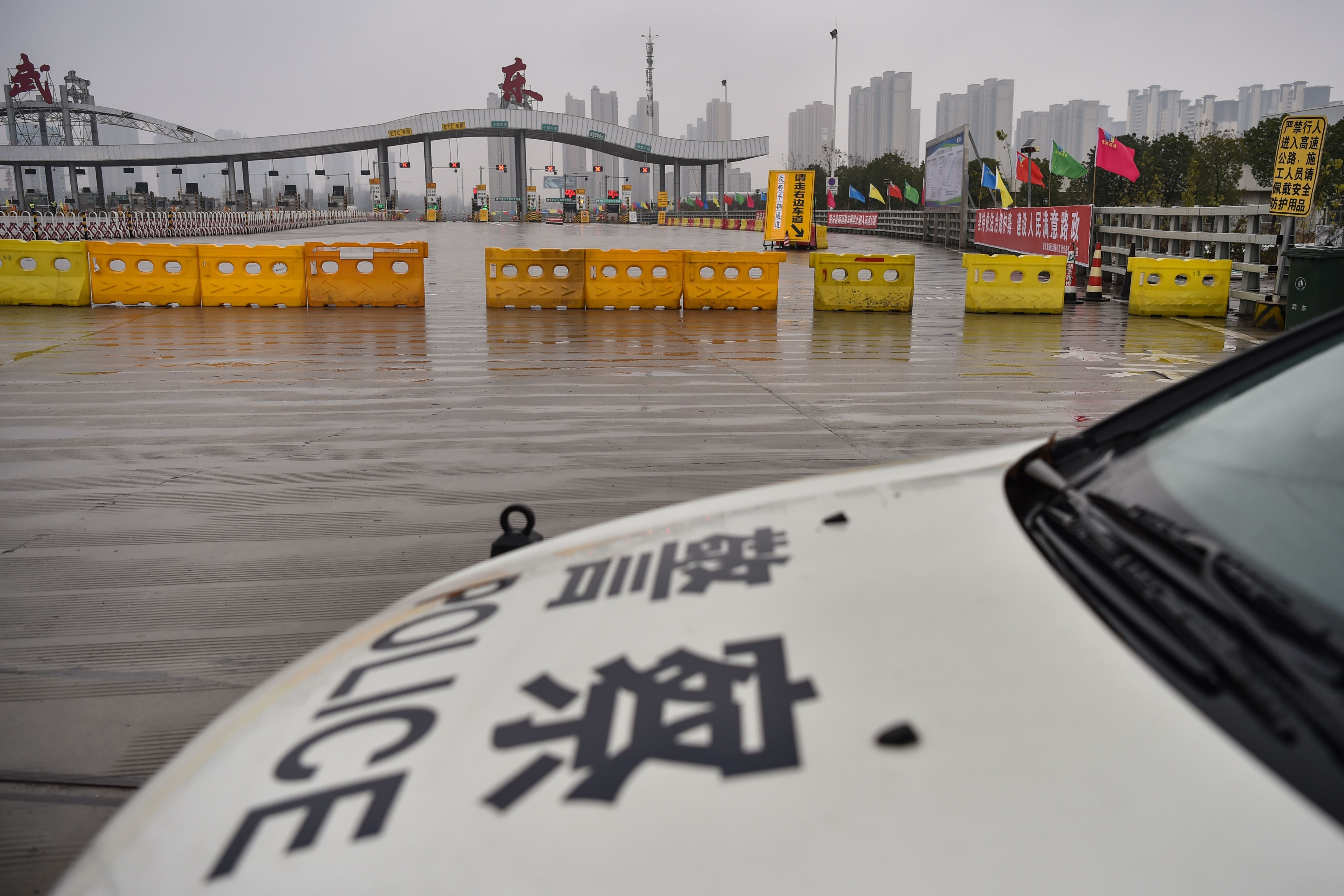 A police car is seen in front of one of the roads blocked by authorities to restrict people leaving Wuhan in China's central Hubei province on Saturday.