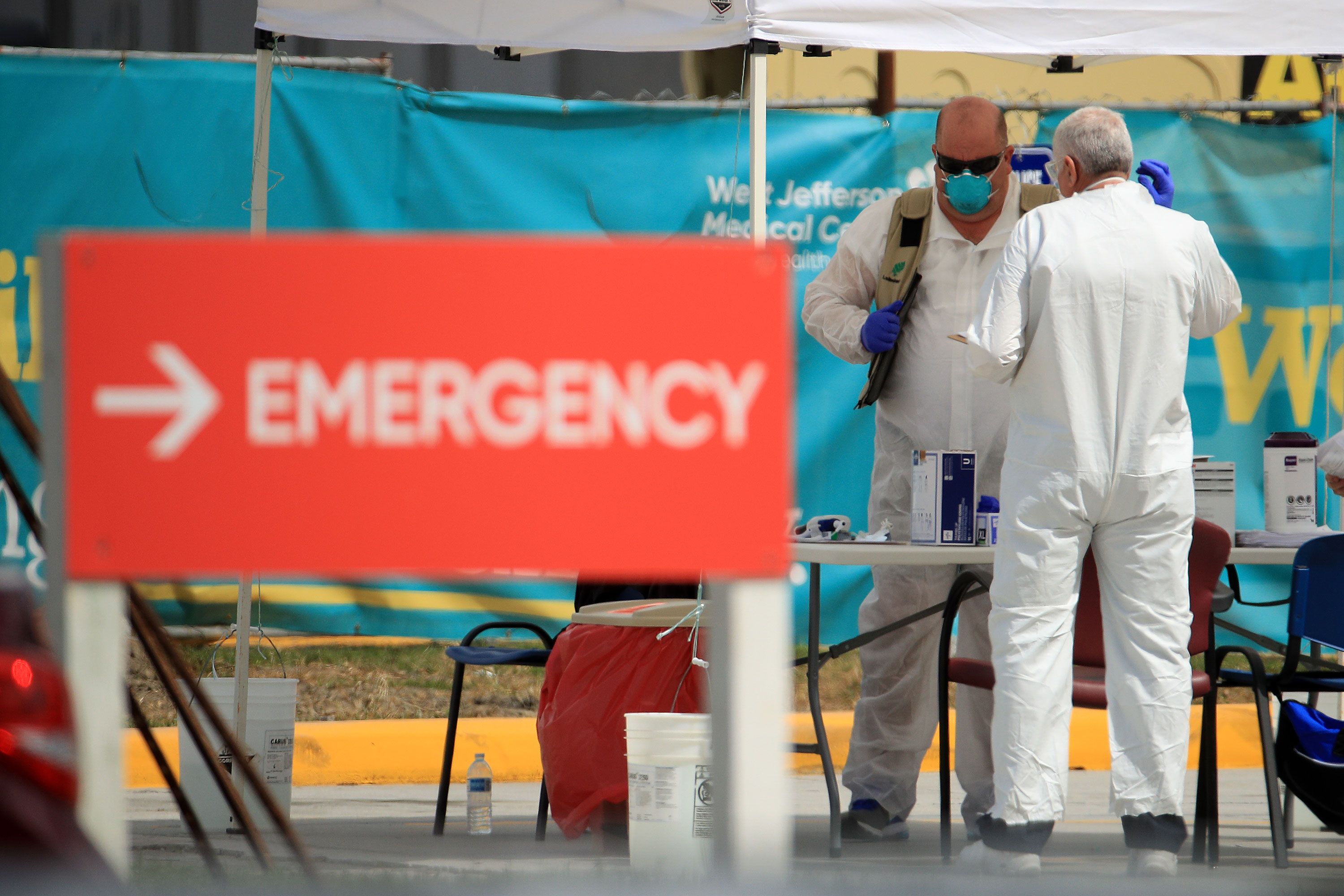 Medical personnel work at a drive-thru coronavirus testing station on March 17 in New Orleans, Louisiana.