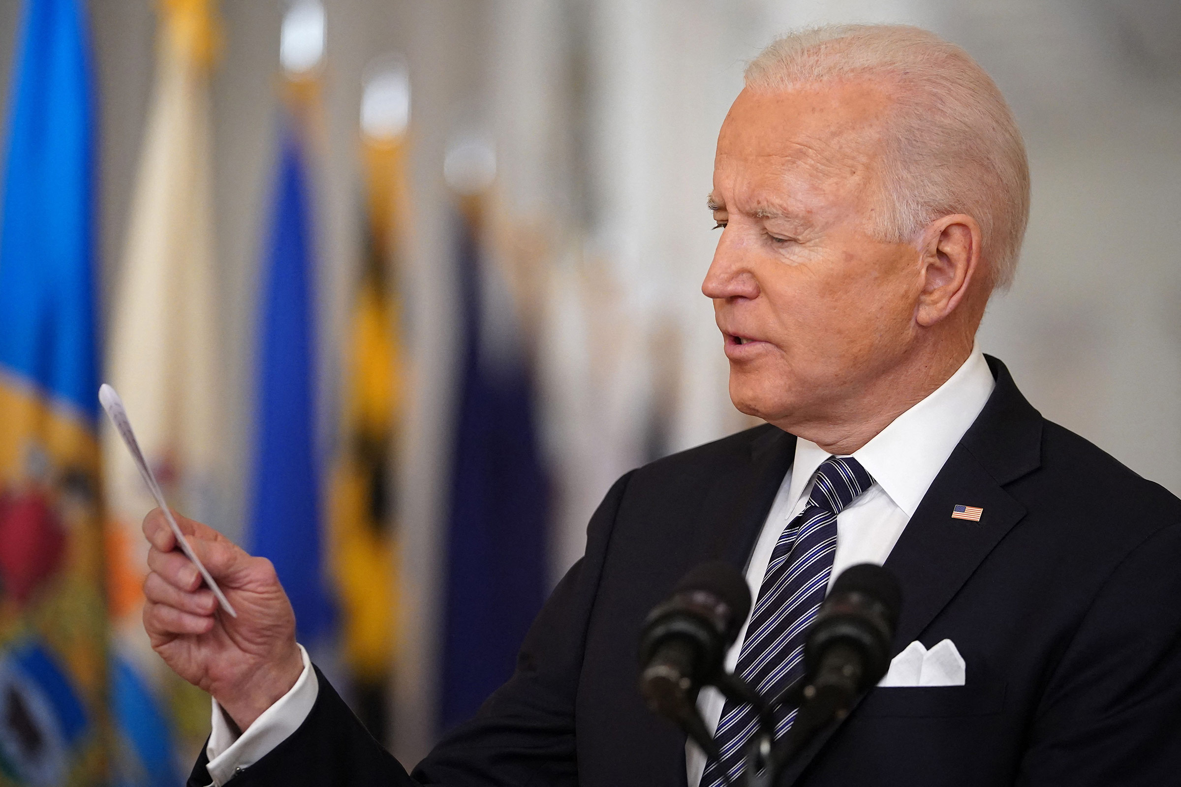 President Joe Biden looks at a card he pulled from his pocket to read the number of Americans who have died of Covid-19 to date, as he speaks on the anniversary of the start of the Covid-19 pandemic, at White House in Washington, DC on March 11.