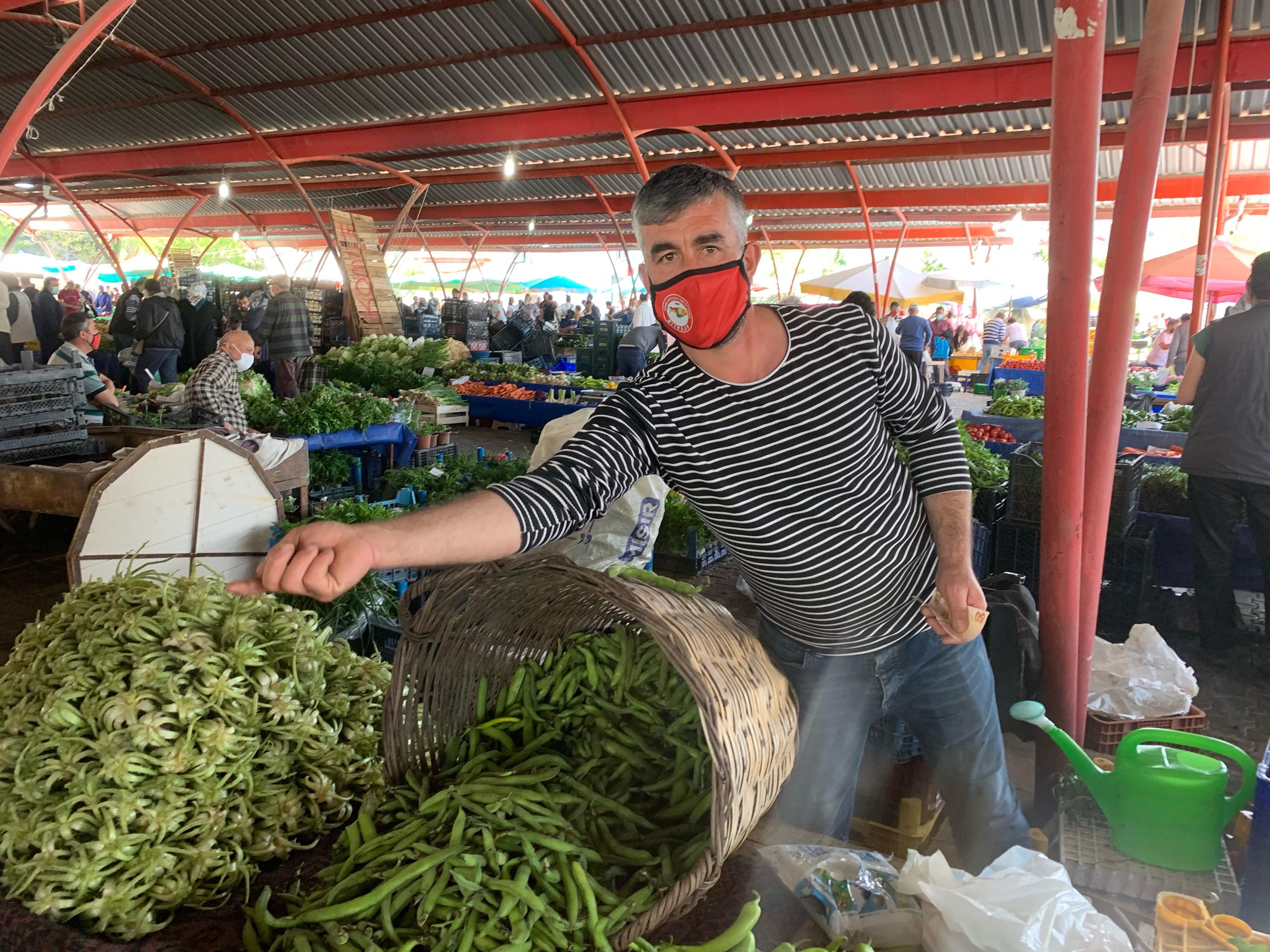 """Vegetable seller Hakan Keskin, 40, is pictured at the farmers market in Ayvalik, Turkey. """"This is our last chance before 3 hard weeks ahead. It's going to be difficult our vegetables are going to get old and we won't be making any money. It's going to be hard days ahead for us."""""""