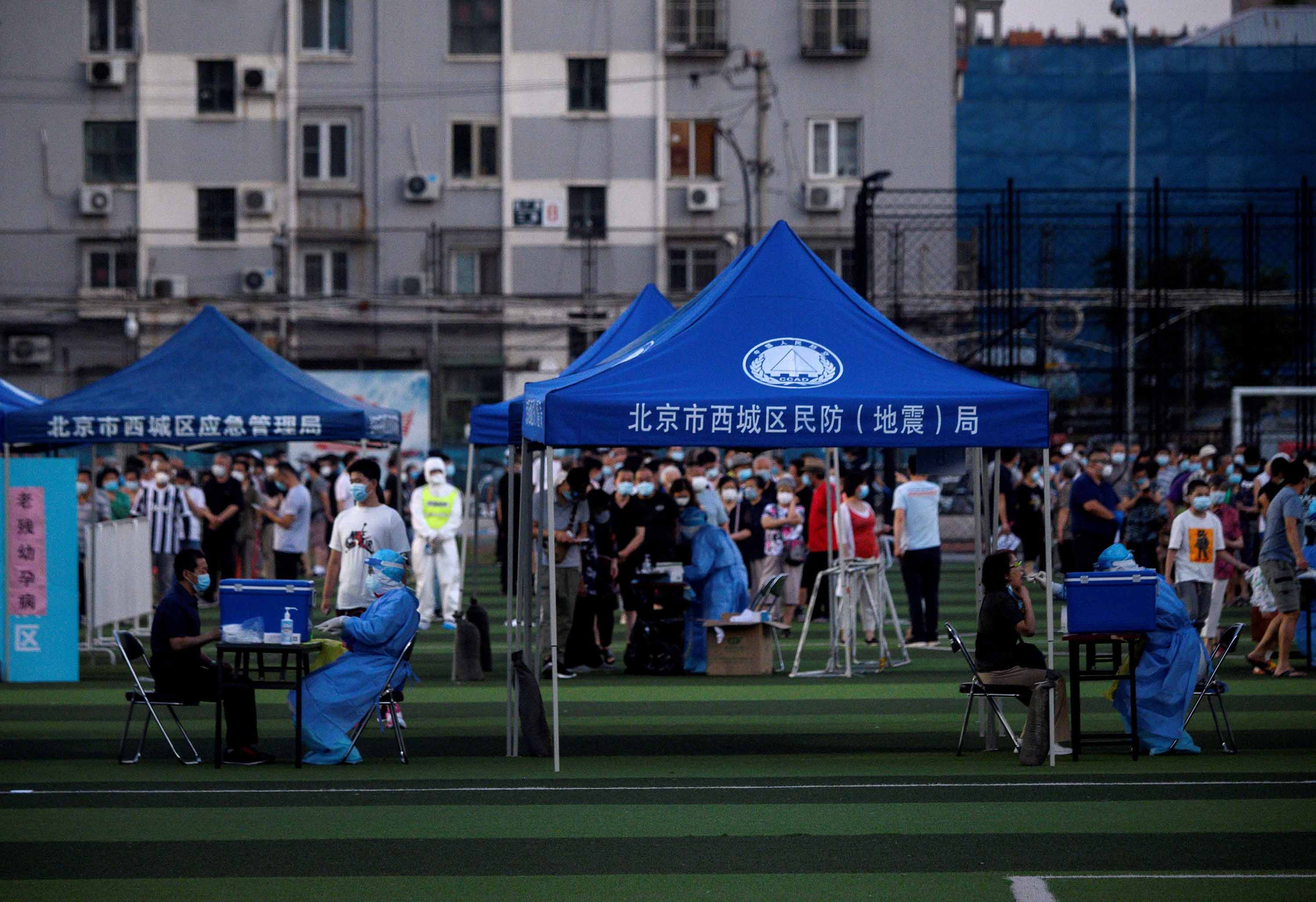 People who visited or live near the Xinfadi food market queue for coronavirus swab testing at Guang'an Sport Center in Beijing, on June 14.