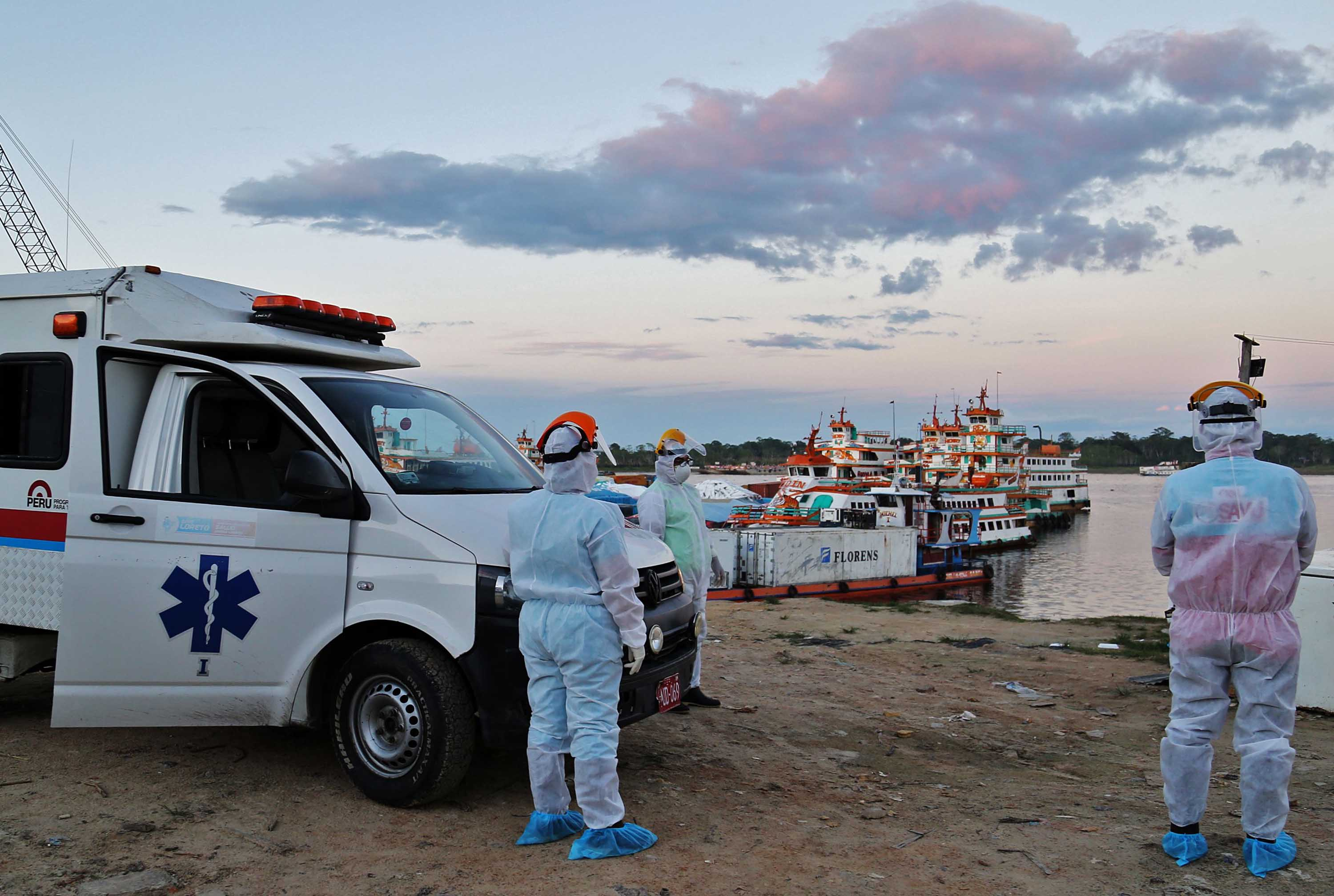 Medical staff wait at a port to transfer COVID-19 patients brought from nearby communities in Iquitos, Peru, on June 18.