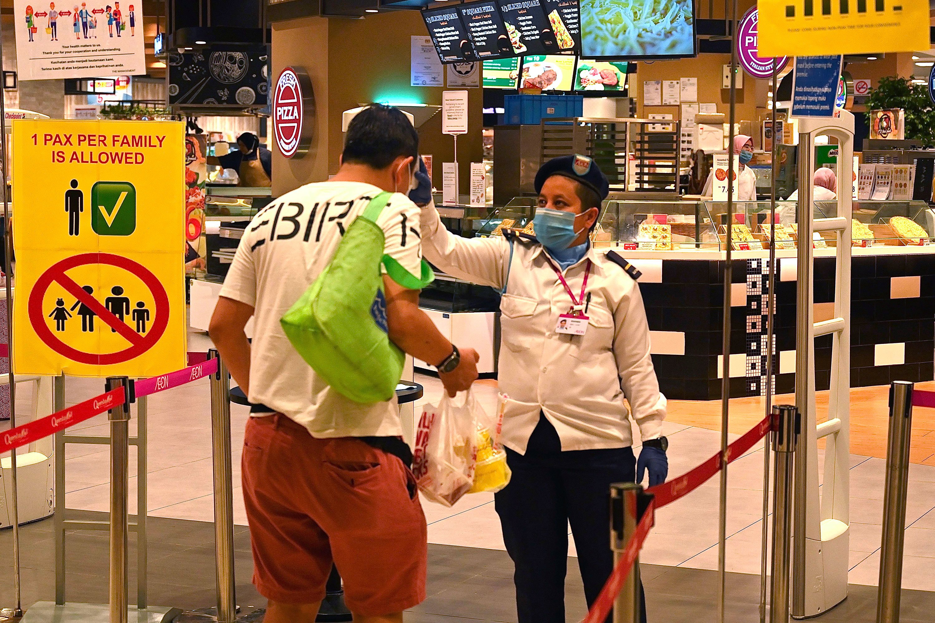 A security guard checks the temperature of a customer arriving at a supermarket in Penang, Malaysia on March 27.