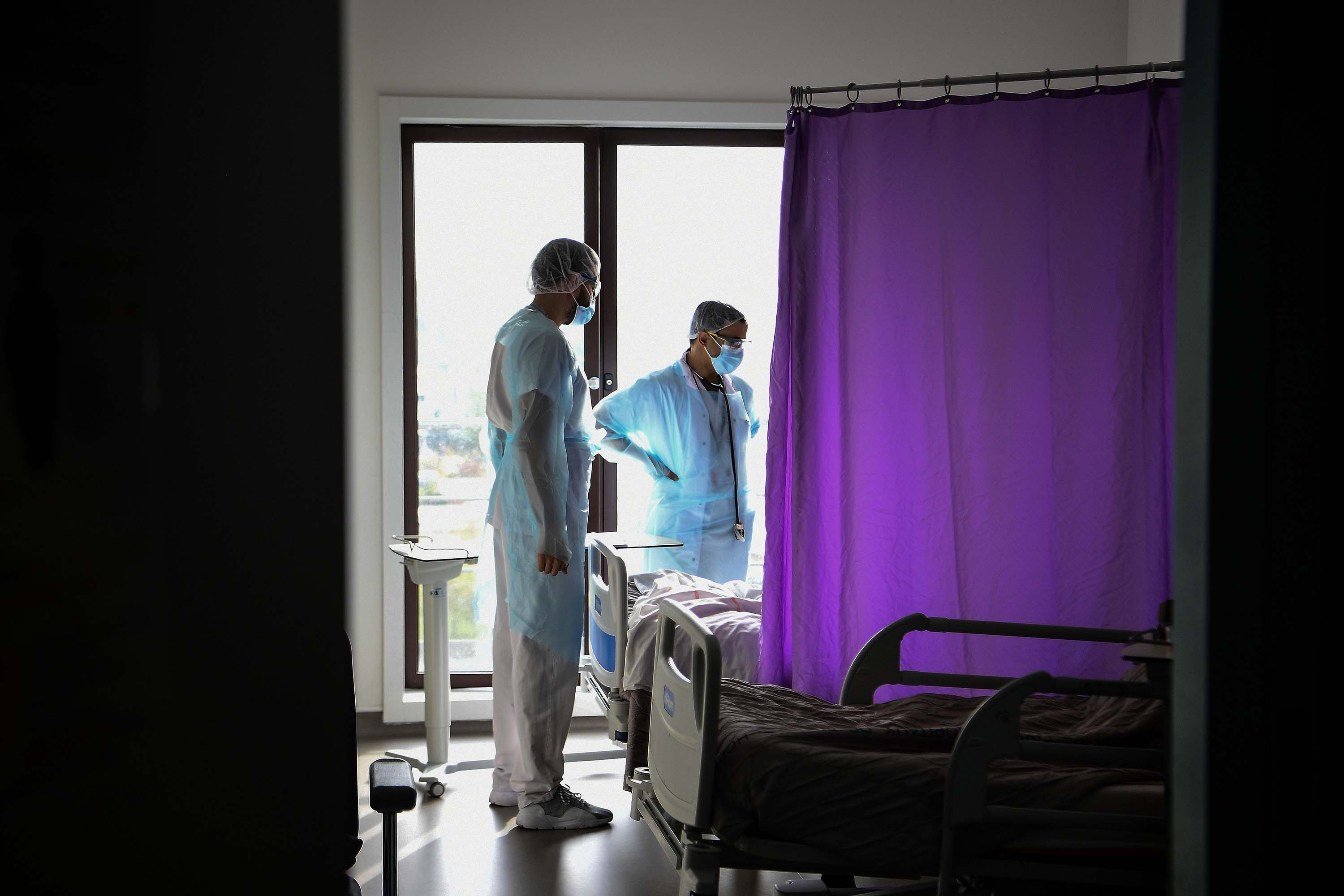 Medical staff members speak to a patient infected with Covid-19 in the infectious diseases unit of the Gonesse hospital in Gonesse, north of Paris, on October 22.