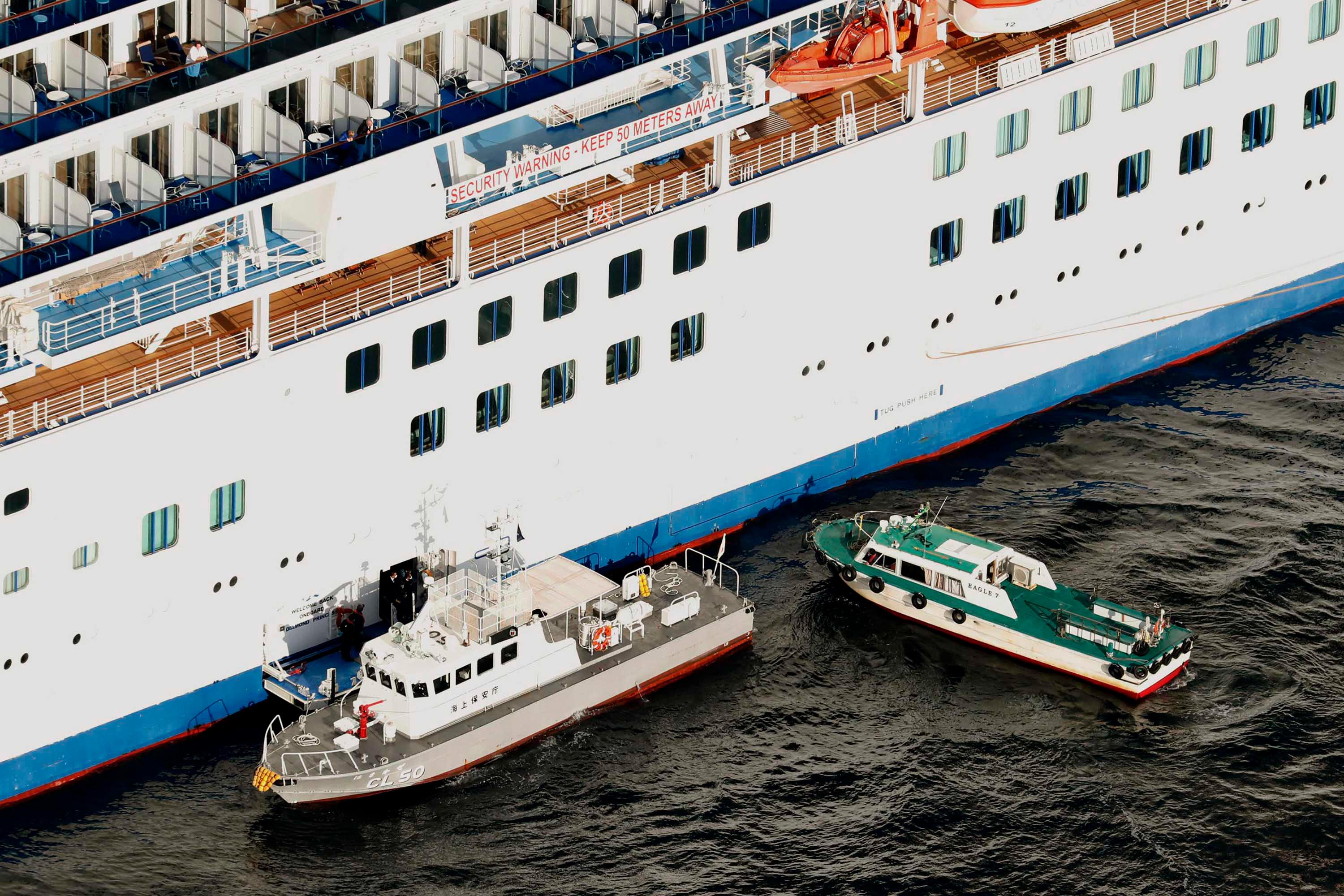 Japan Coast Guard's patrol boat, left, is brought alongside the cruise ship Diamond Princess to take passengers tested positive for coronavirus to hospitals off Yokohama, south of Tokyo, Wednesday, February 5.