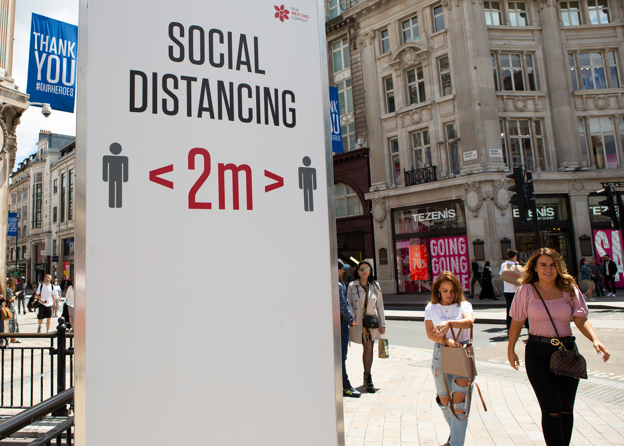 People walk past a social distancing sign in London on July 11.