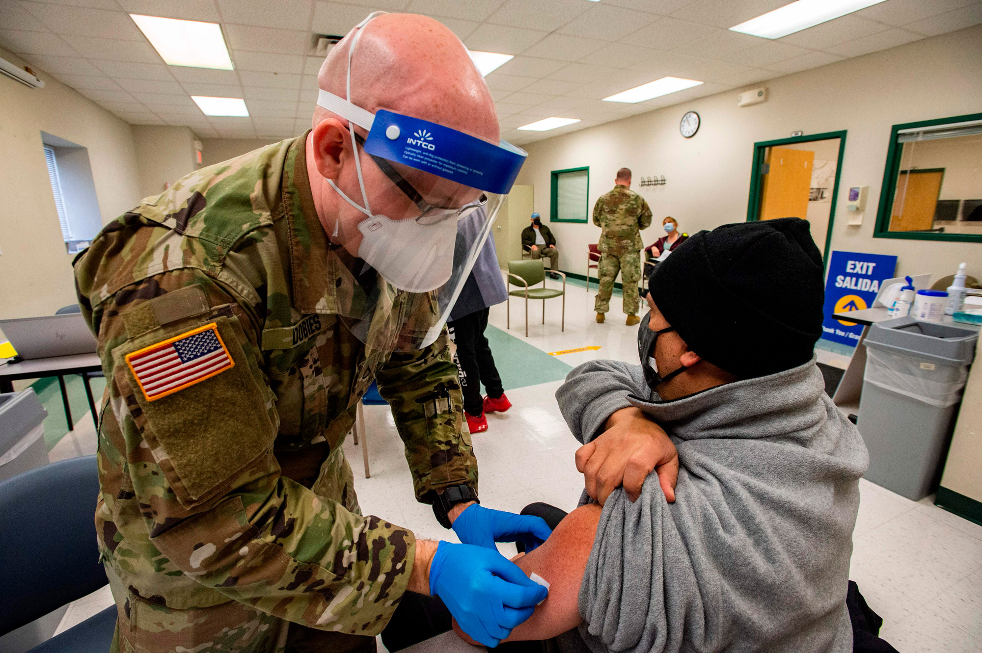 A soldier prepares to vaccinate a man at an East Boston Neighborhood Health Center Vaccination Clinic in Boston on February 16.