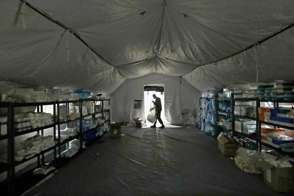A U.S. Army soldier walks inside a mobile surgical unit being set up by soldiers from Fort Carson, Colorado, and Joint Base Lewis-McChord as part of a field hospital inside CenturyLink Field Event Center, Tuesday, March 31, in Seattle.