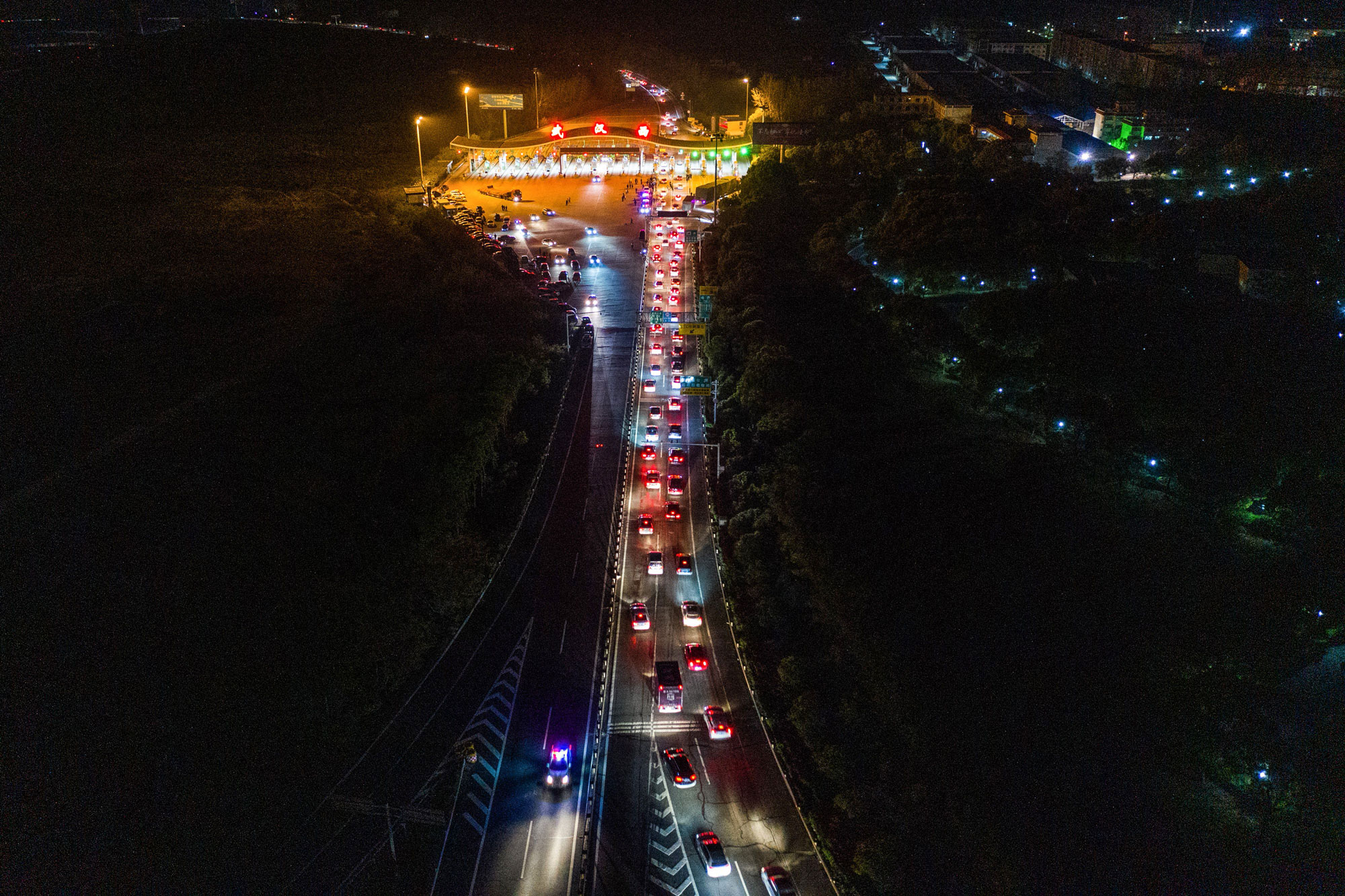 This photo taken early on Wednesday shows cars queuing to leave Wuhan at a highway toll station.