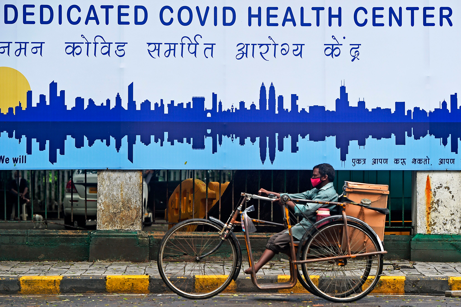A man rides in front of a Covid-19 health center in Mumbai on July 7.