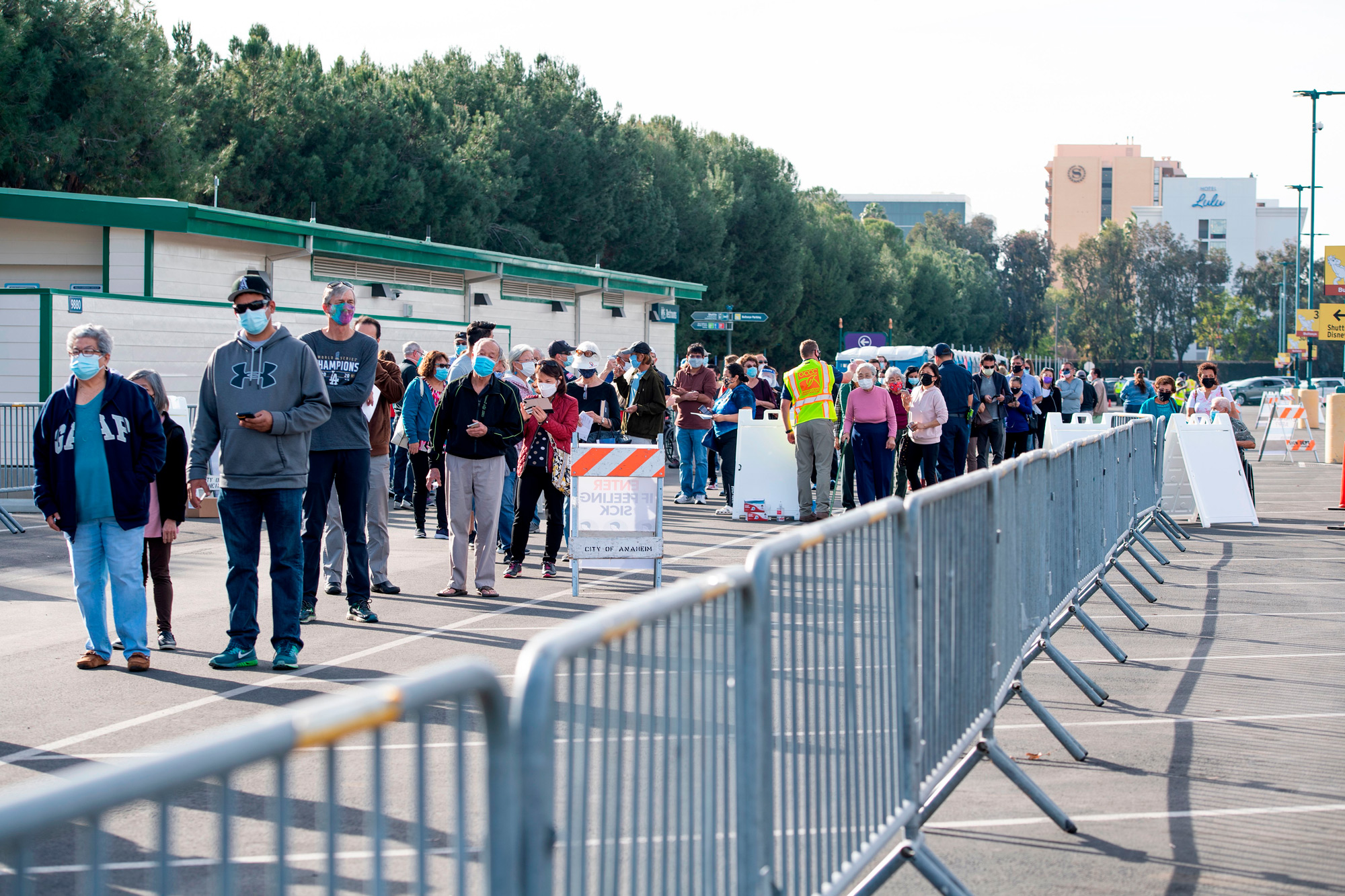 People wait in line in a Disneyland parking lot to receive Covid-19 vaccines on January 13 in Anaheim, California.