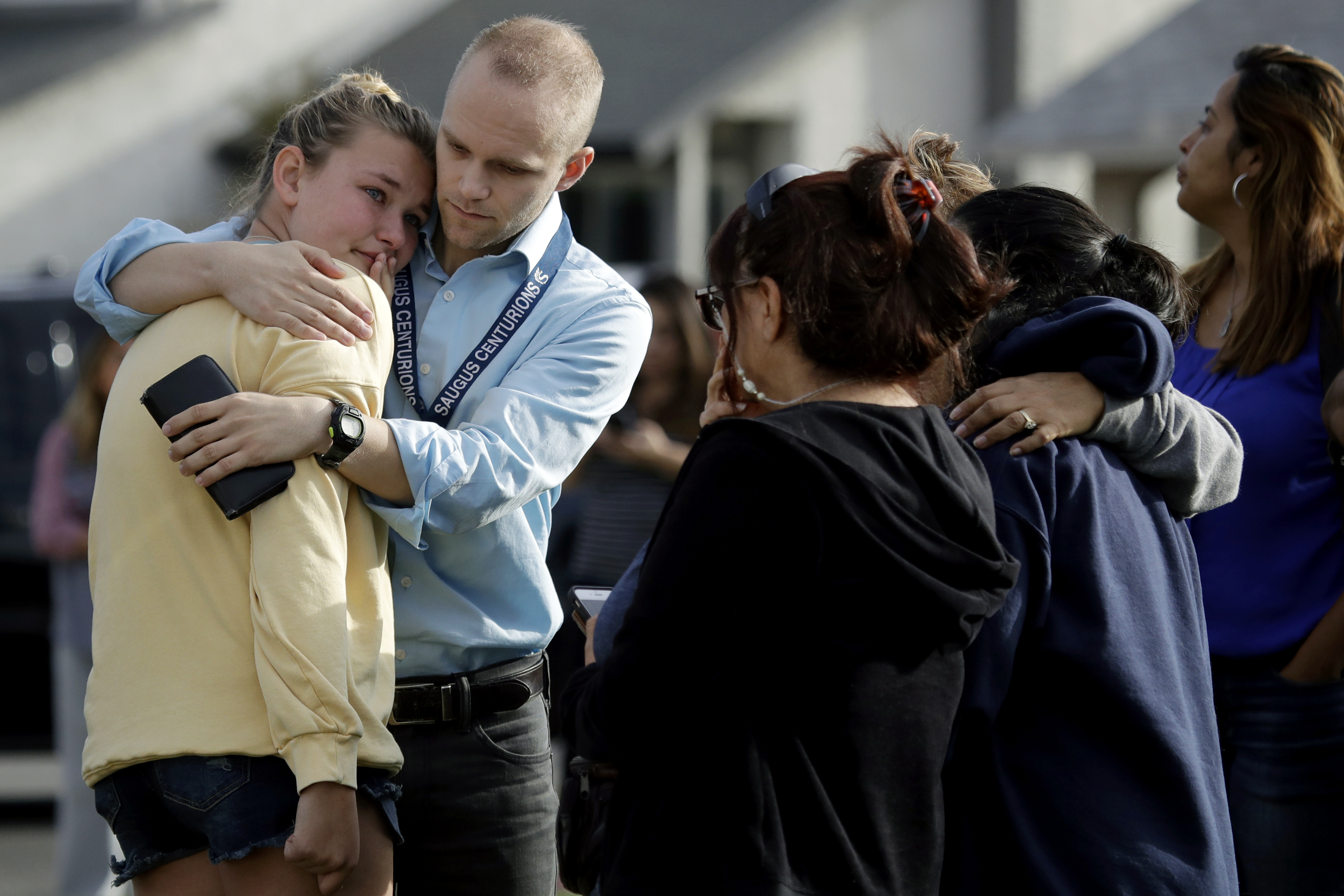 D.J. Hamburger, center in blue, a teacher at Saugus High School, comforts a student after reports of a shooting at the school on Nov. 14 in Santa Clarita, California.